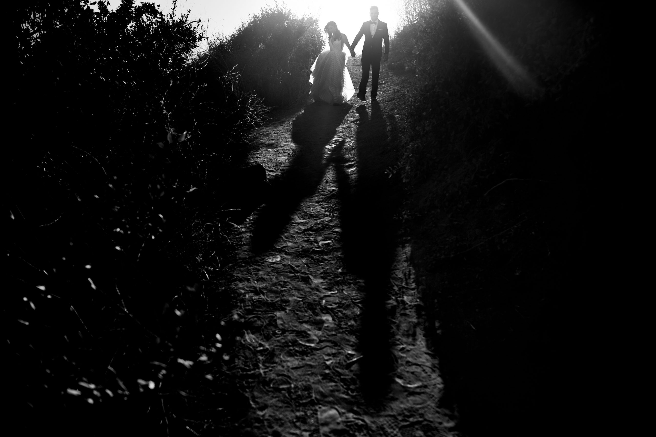 The sun shines behind the newly-wed couple as they make their way down a hill