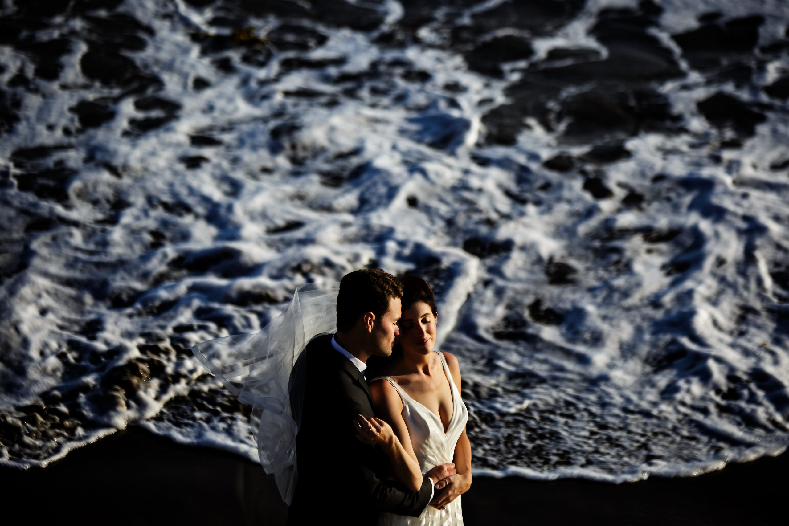 The veil flies as bride and groom embrace in front of ocean waves
