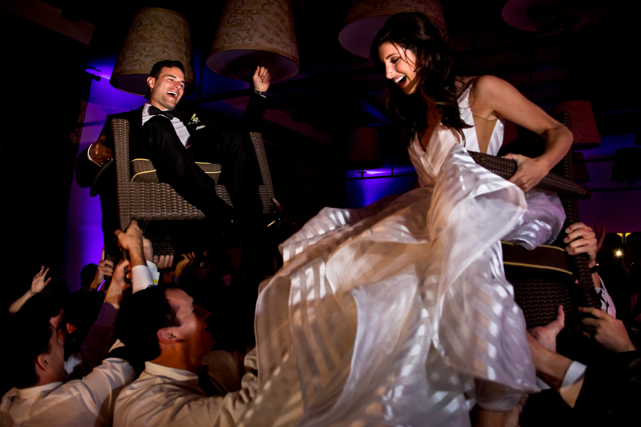 Bride and groom are seen both crowd-surfing in chairs
