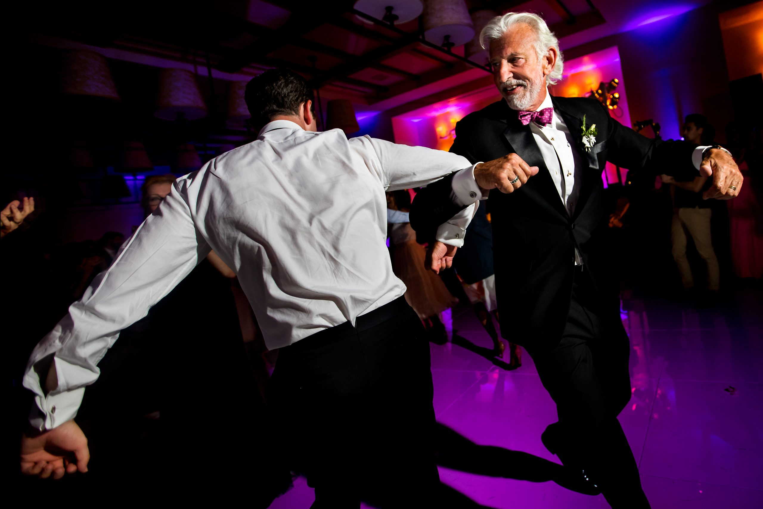 Two men dance on dance floor linking arms