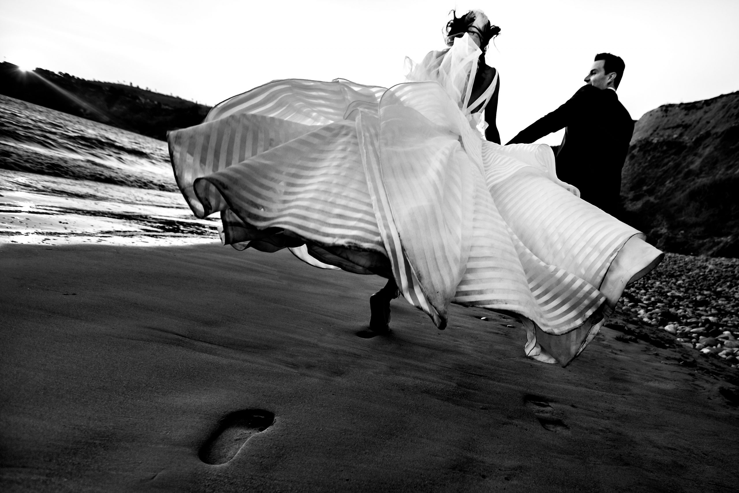 Bride and groom leave footprints in the sand as they run across the beach