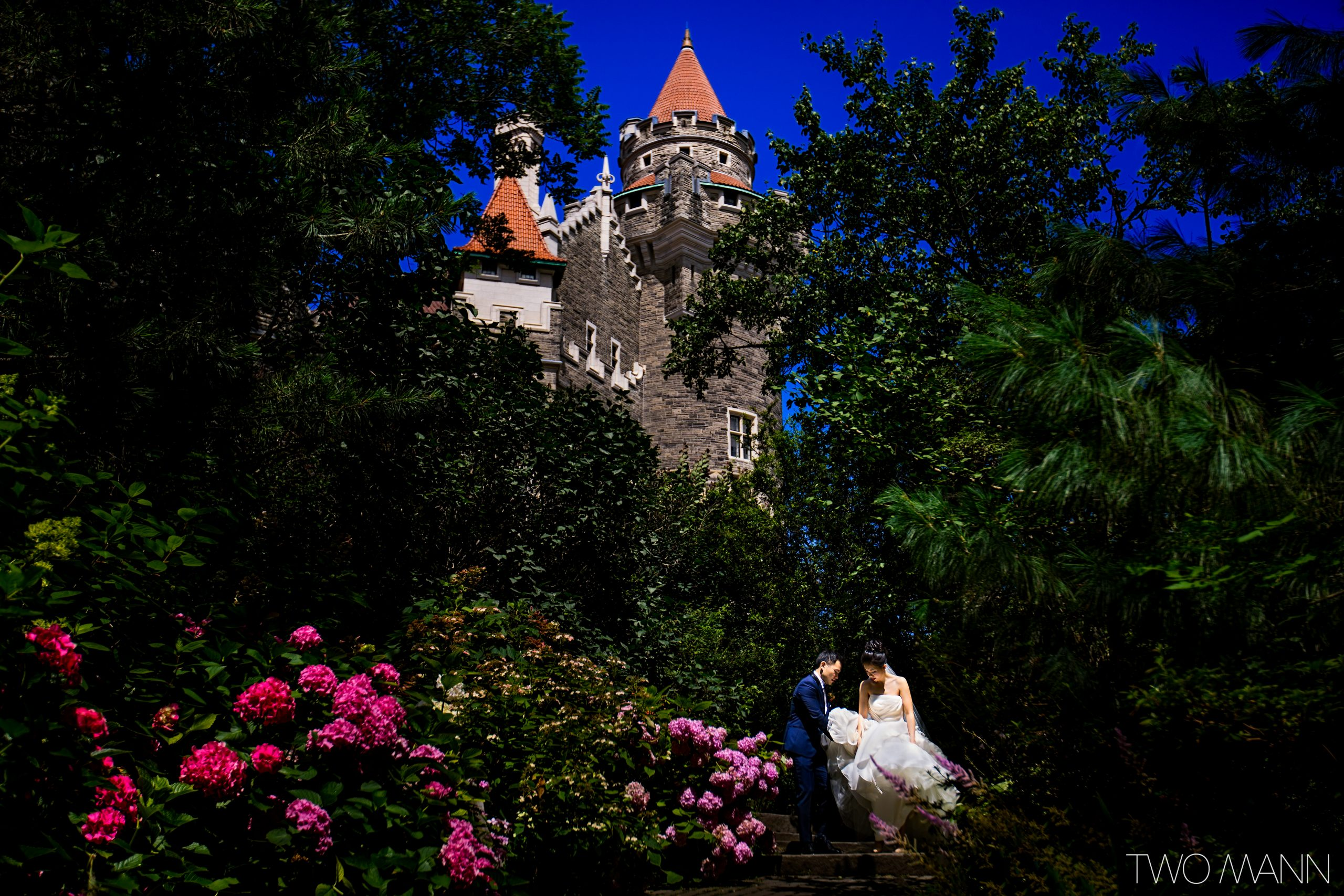 groom helping bride down stairs amongst flowers with castle behind