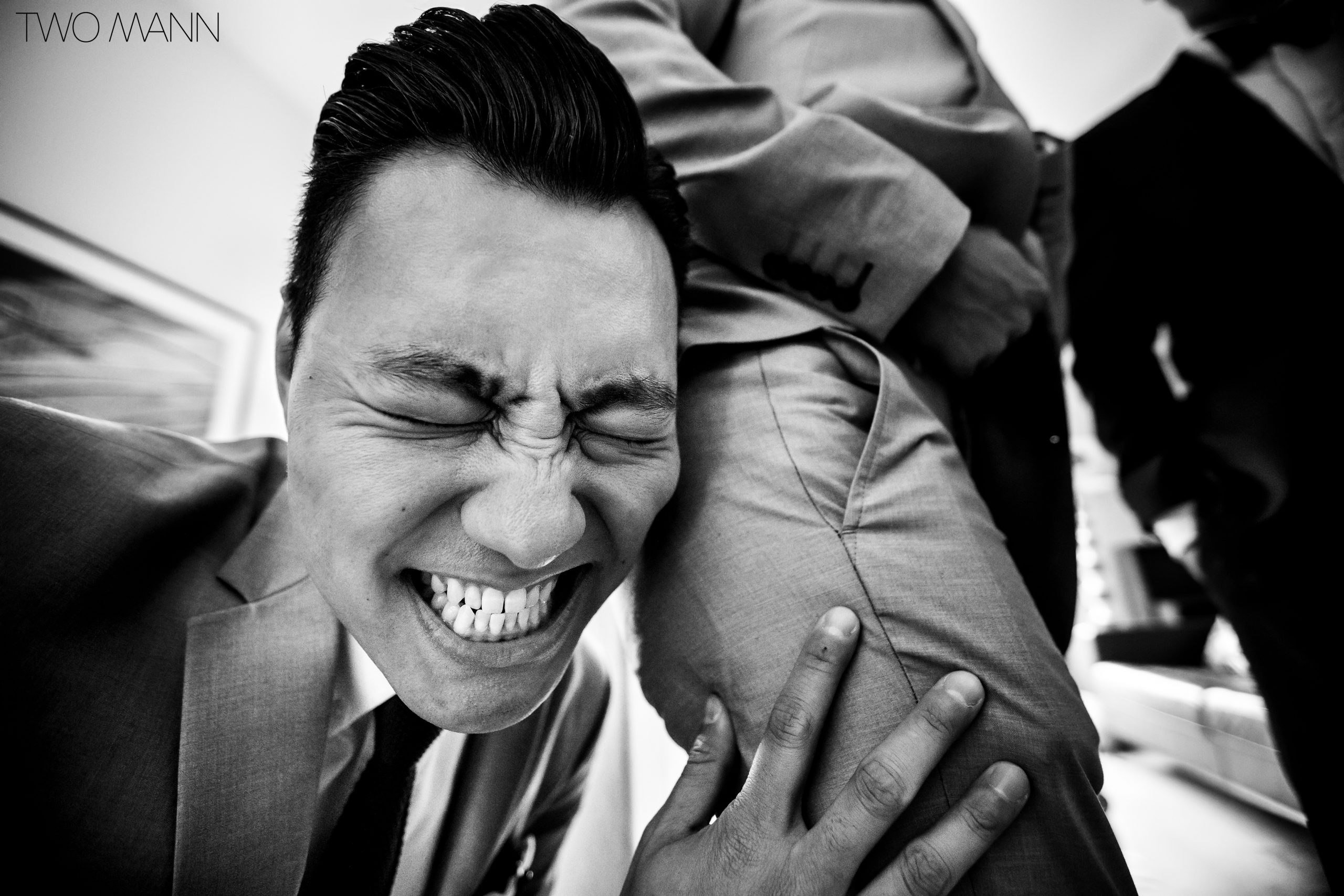 chinese groomsman with face on groomsman bum during door games at chinese wedding