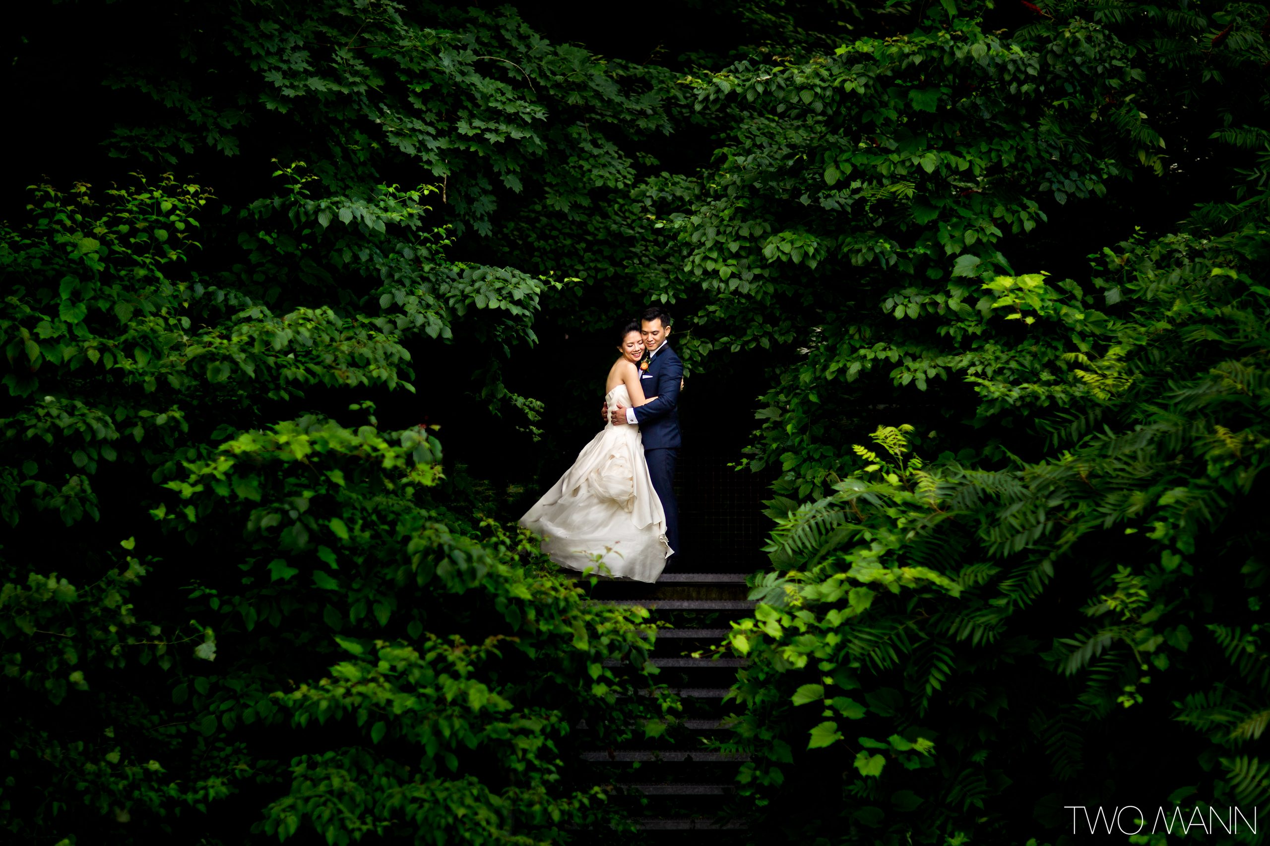 bride and groom portrait surrounded by green leafy trees