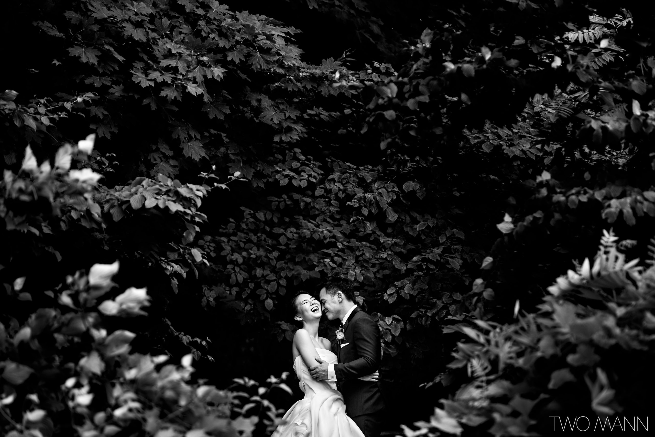 black and white wedding portrait with bride and groom surrounded by trees