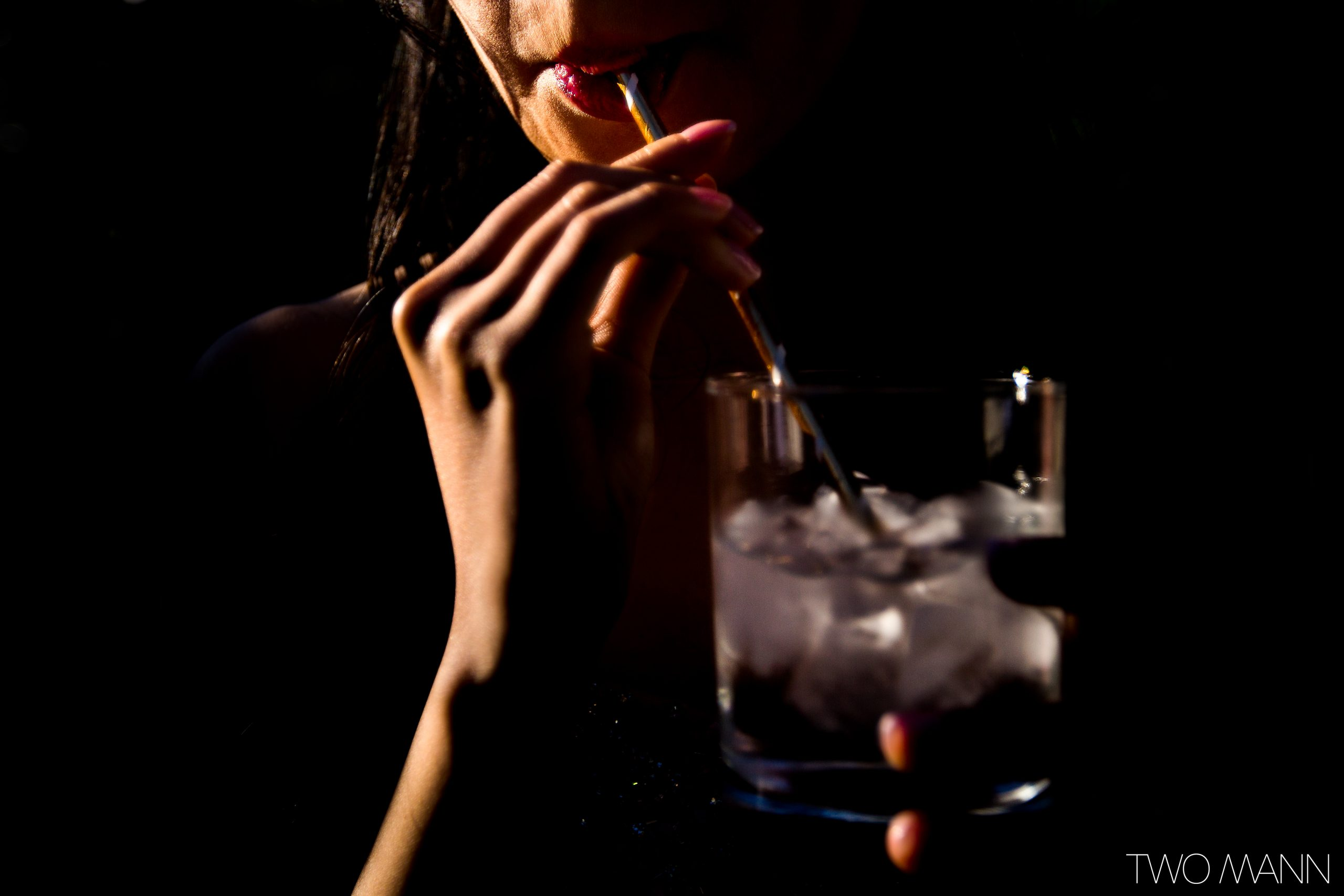 close up of bride sipping cocktail through a straw in dramatic light