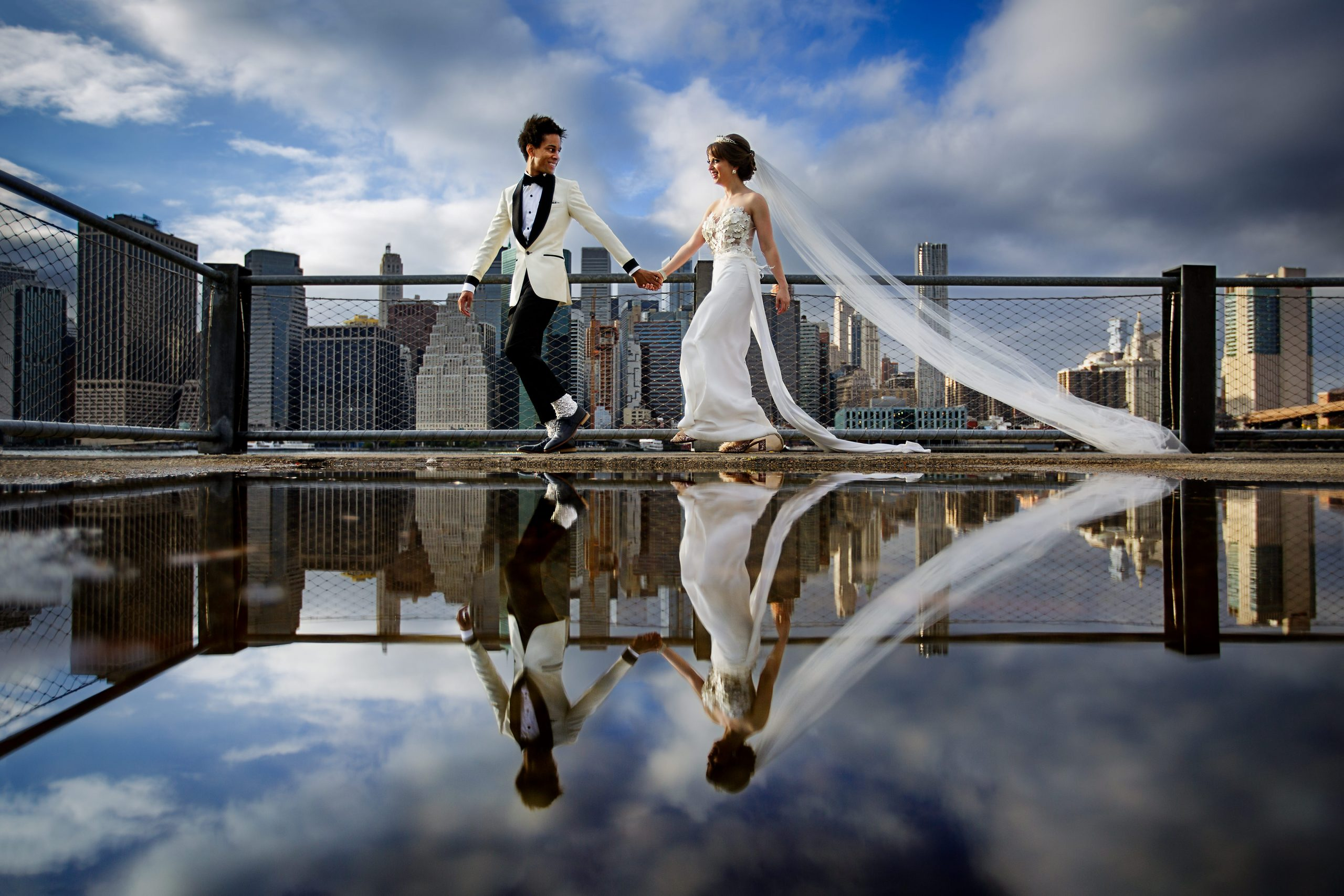 Groom holding bride's hand as they walk across city rooftop which is also reflected by a puddle