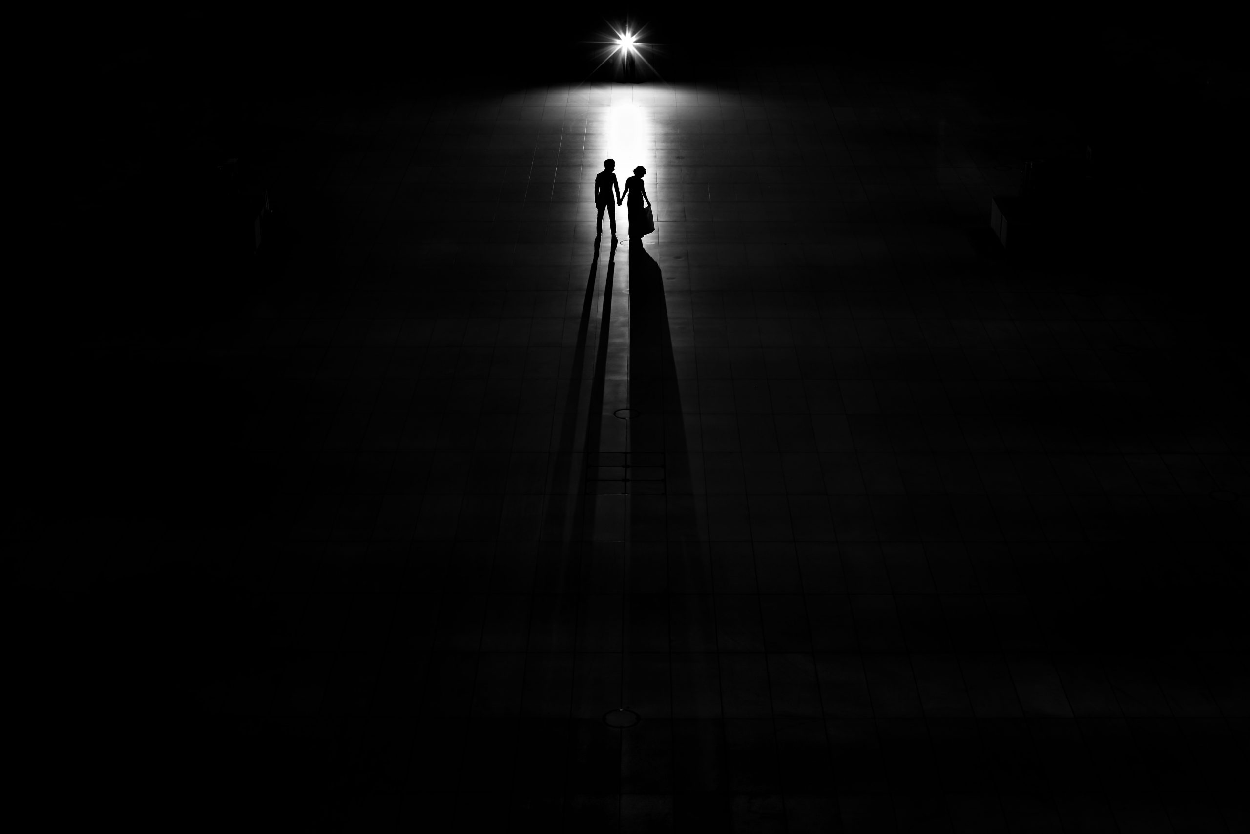 Bride and groom holding hands casts long shadow