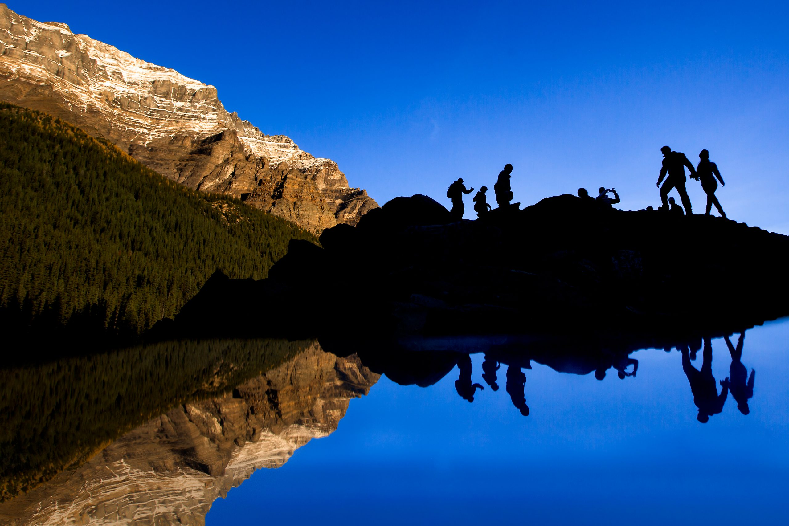 Silhouette of bride and groom and wedding guests standing on top of mountain with their reflection in the lake