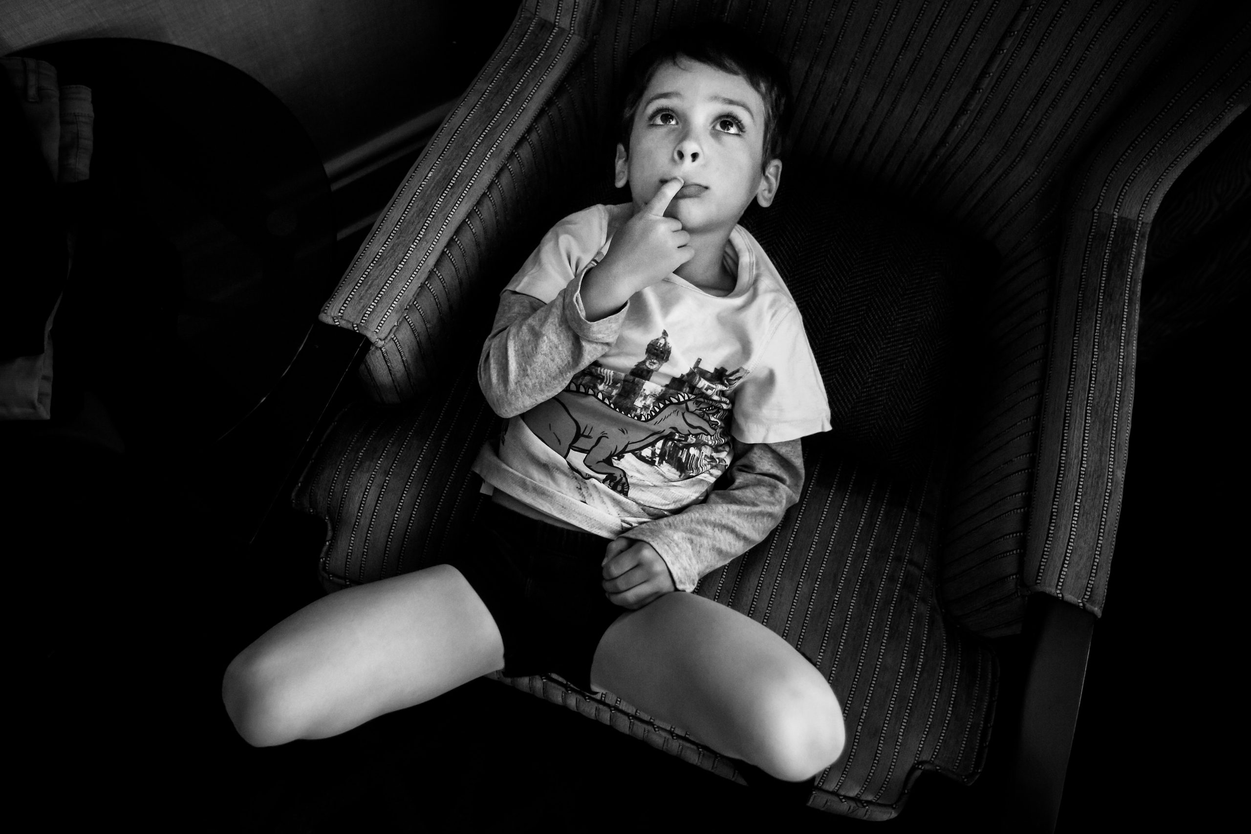 A little boy sits on a sofa with his fingers on his lips