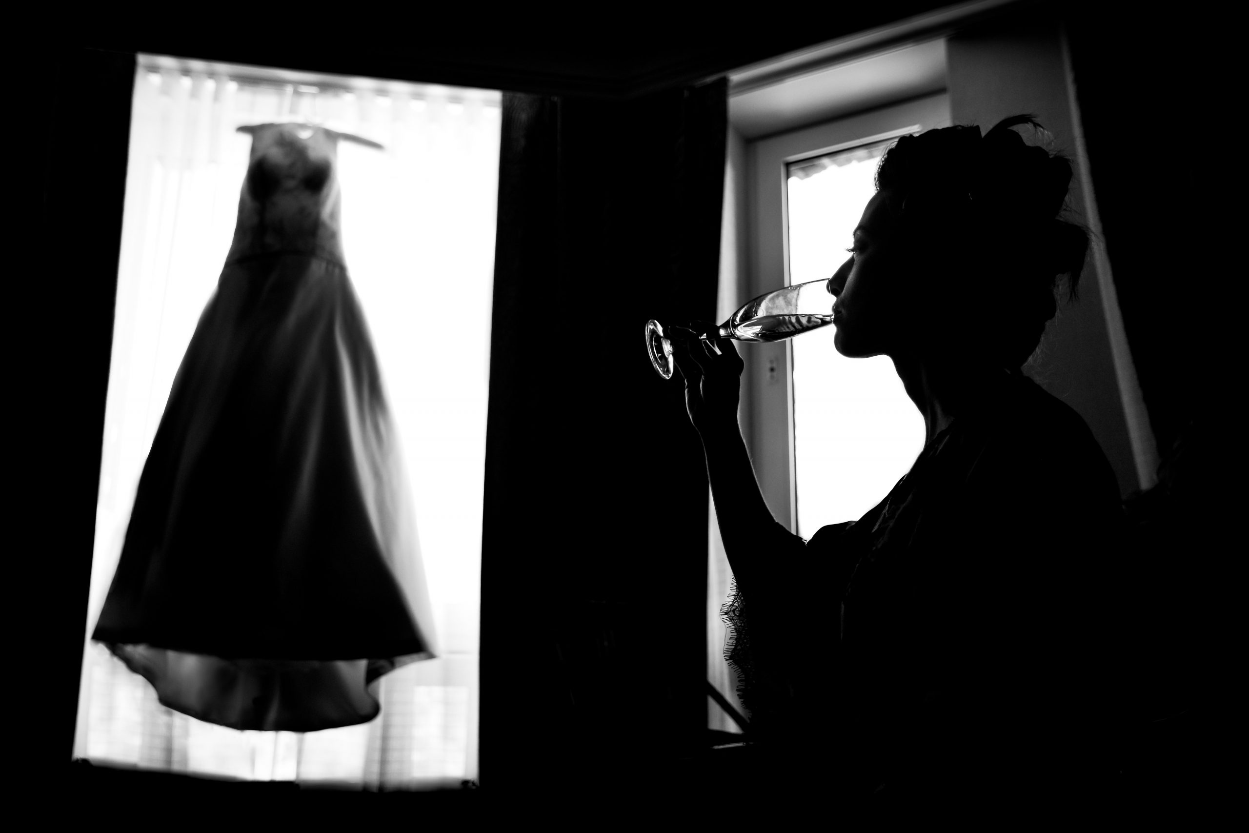 A bride looks at her hanging wedding gown while drinking