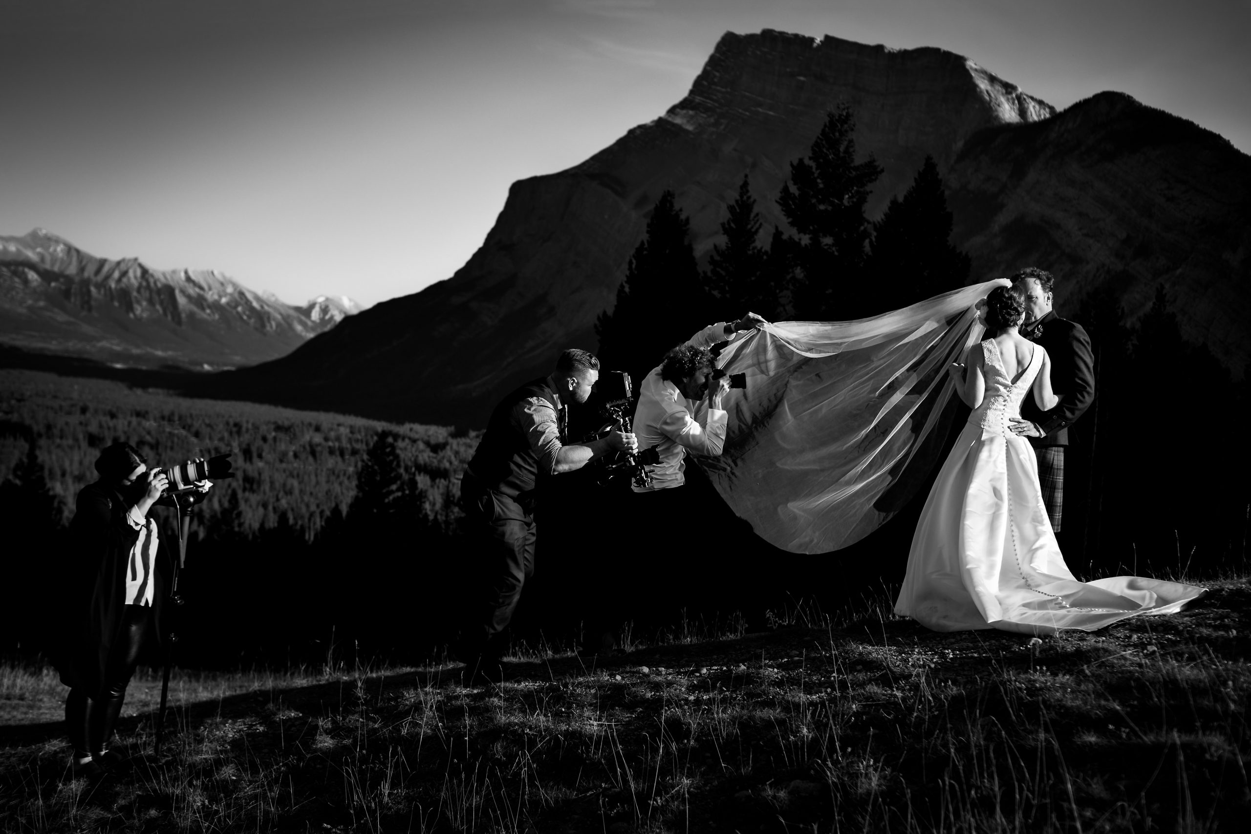 Photographers are ready to shoot pictures of bride and groom on mountain top