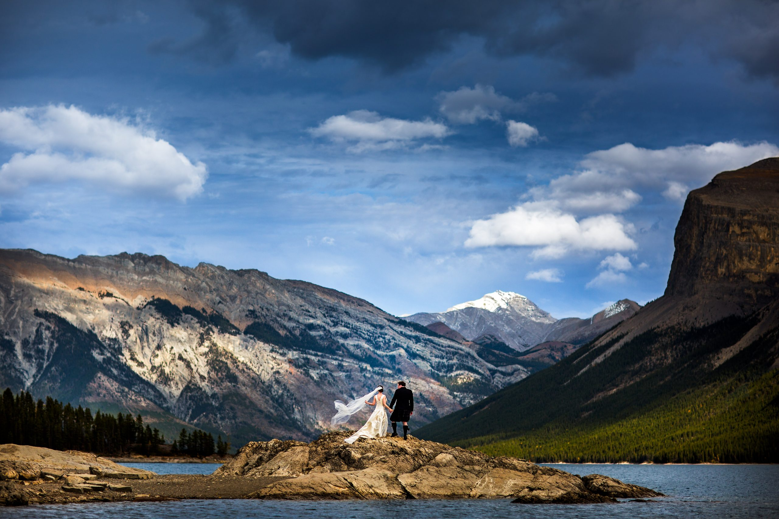 Bride and groom hold hands while standing on rocks in body of water with Rockies as the background