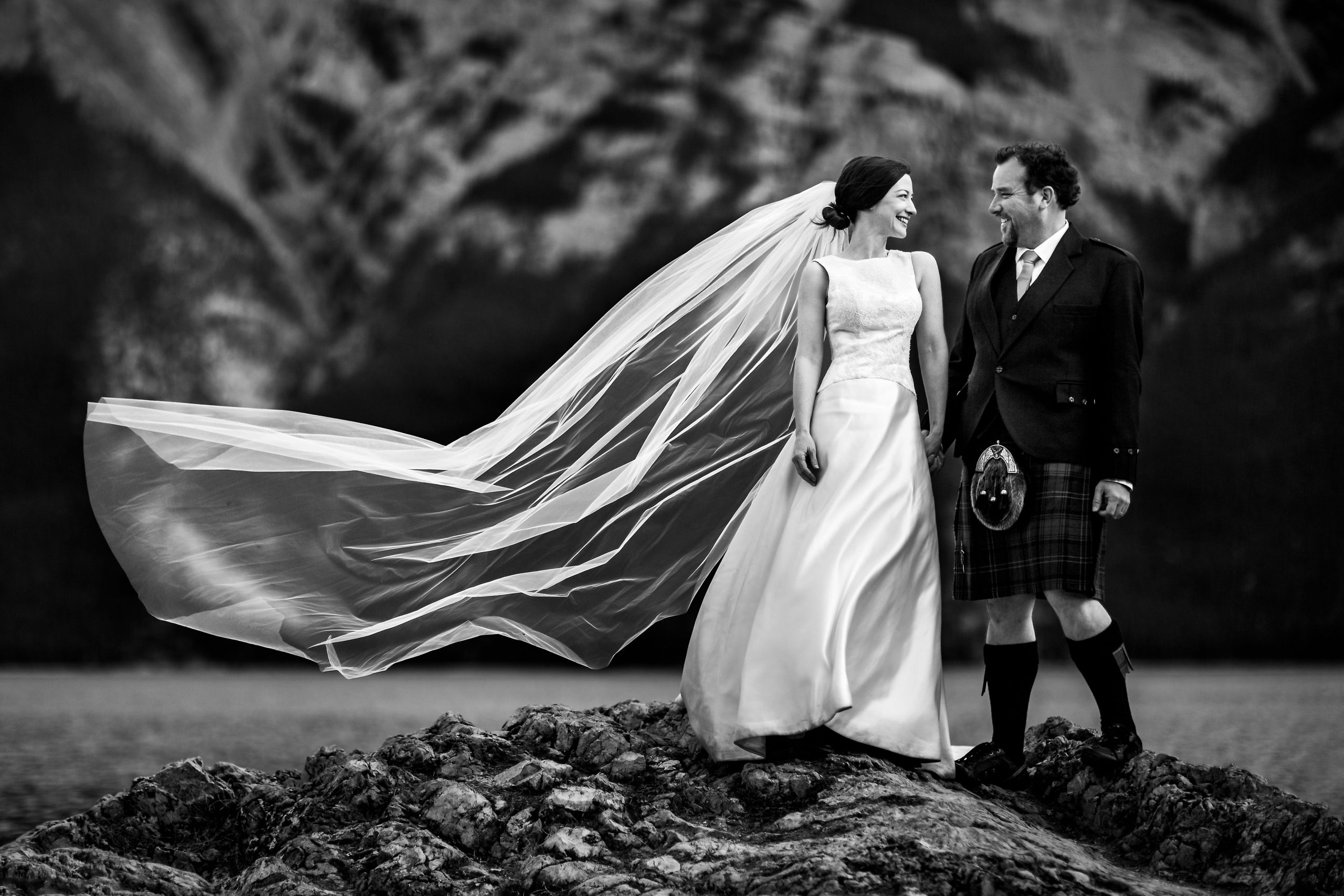 Bride with wedding dress and long veil and groom with Scottish kilt and sporran stand on rocks hand in hand in Banff