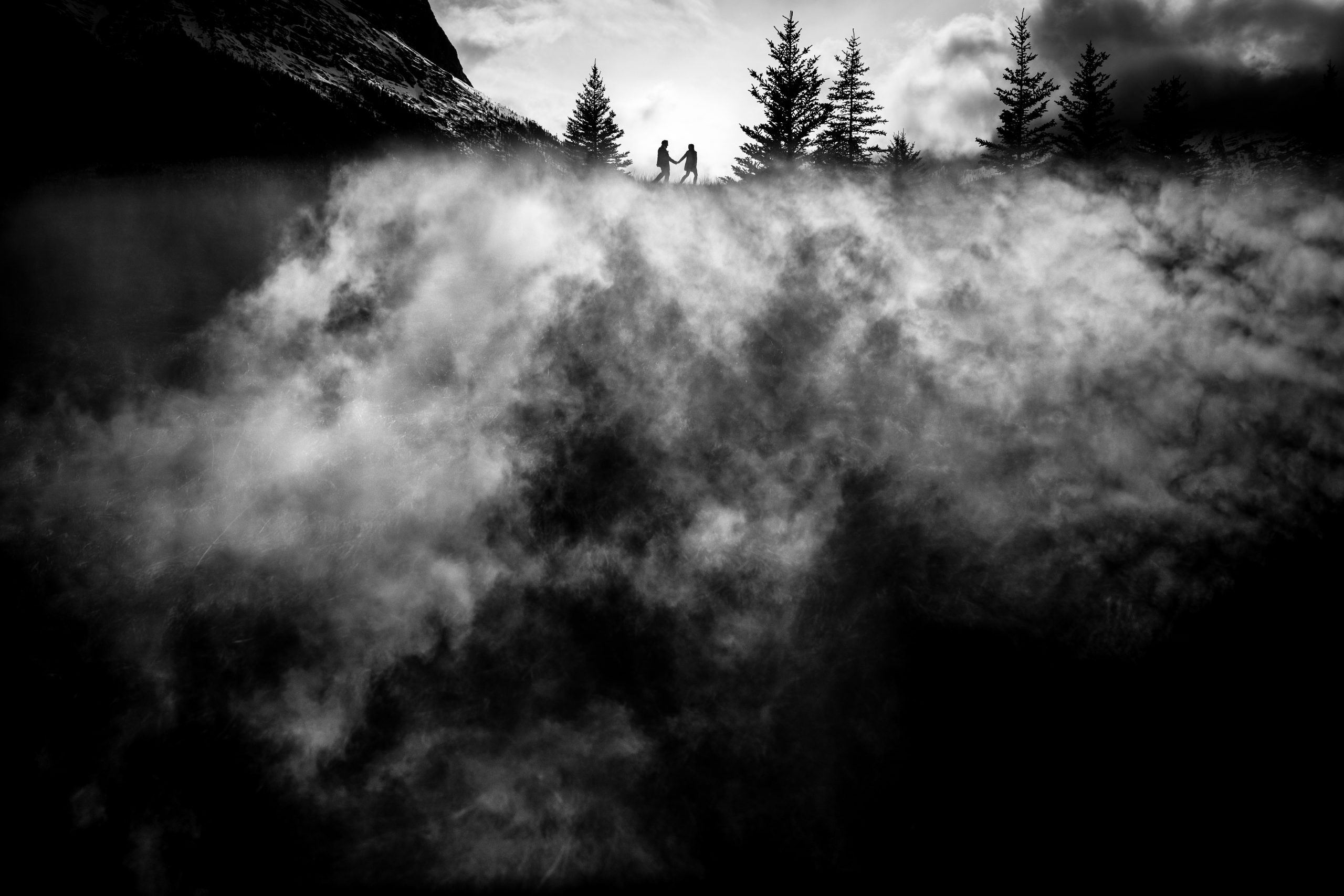 Silhouette of bride and groom walking hand in hand on top of the Rockies shrouded by clouds and fog