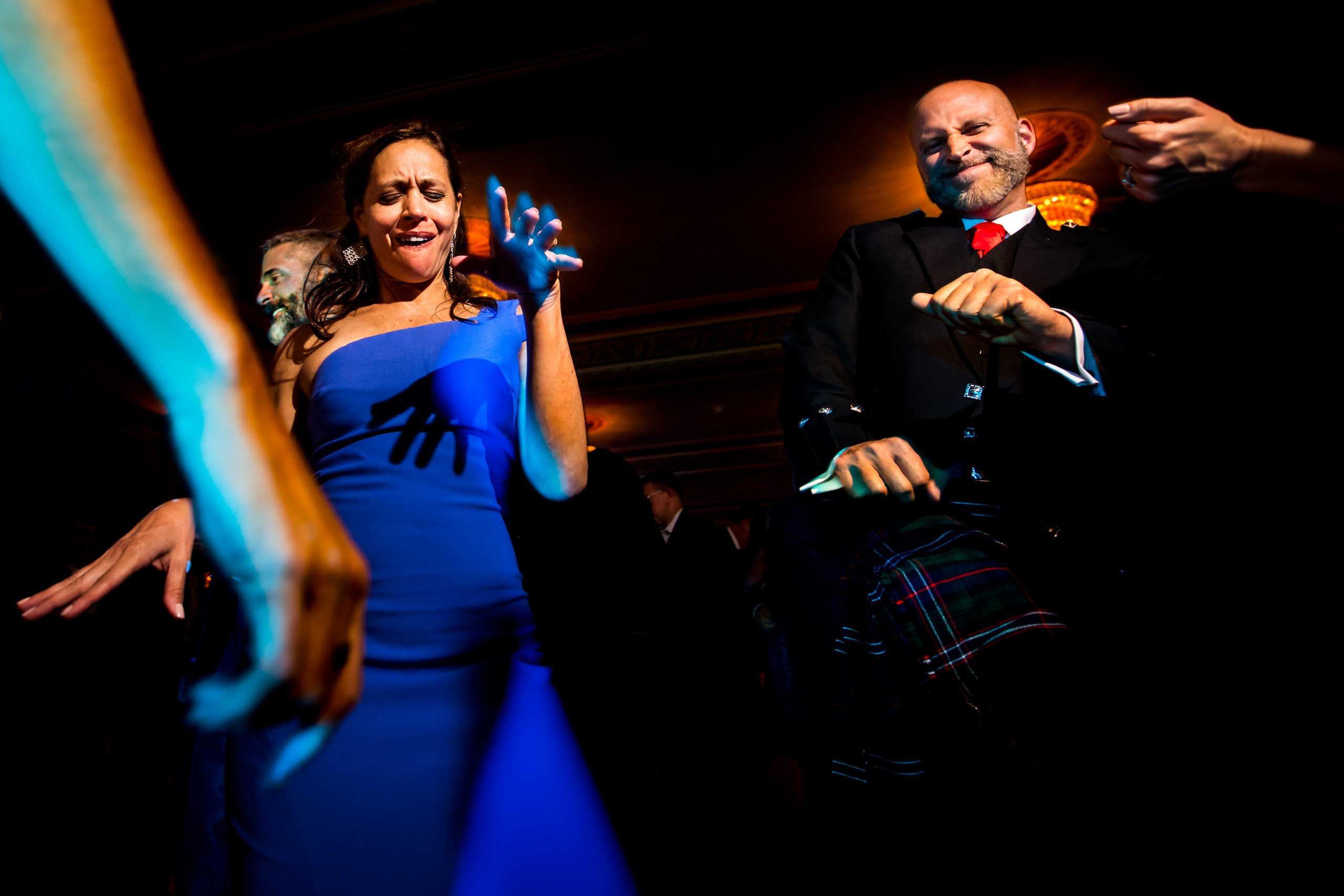 Man in kilt dances with wedding guests at Fairmont Banff Springs Hotel
