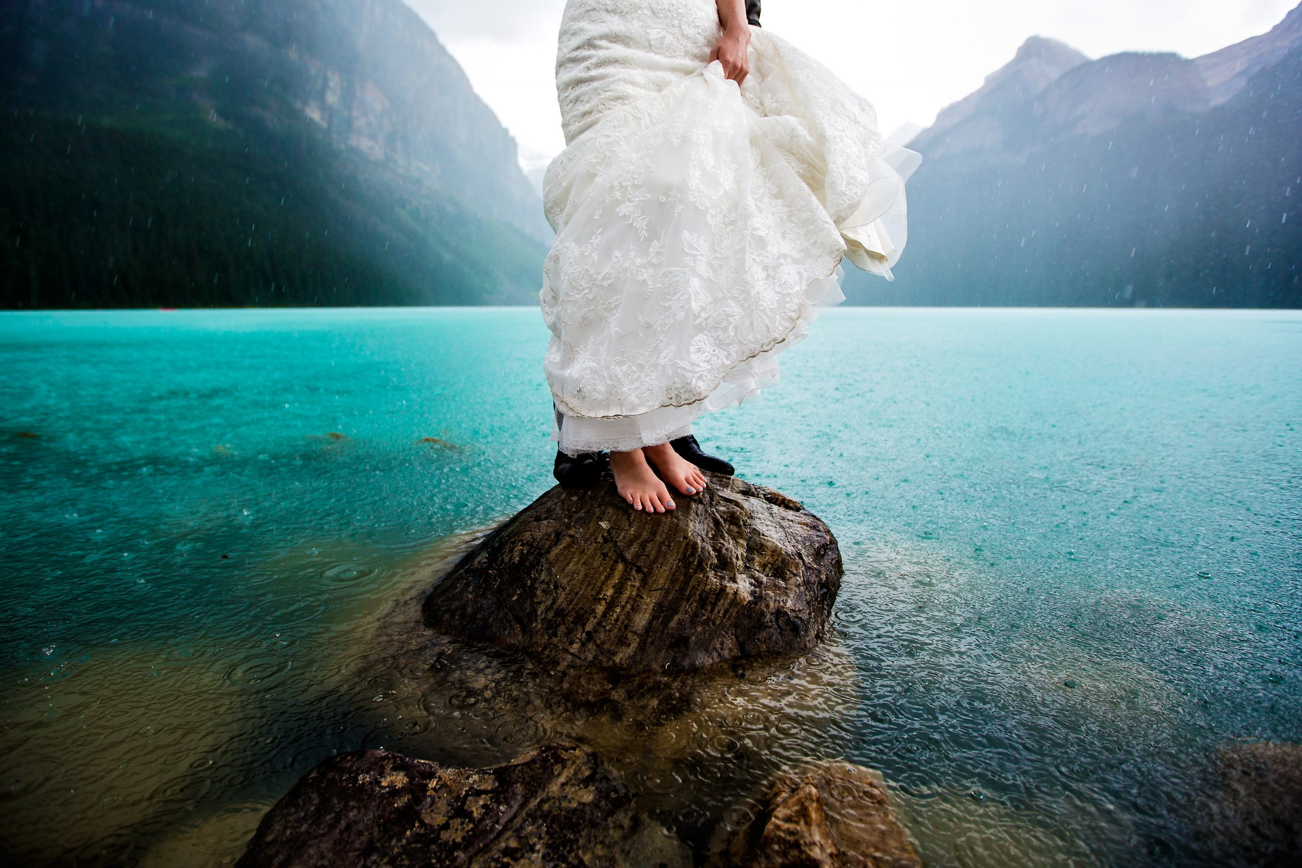 A bride standing on a rock in the waters of Lake Louise
