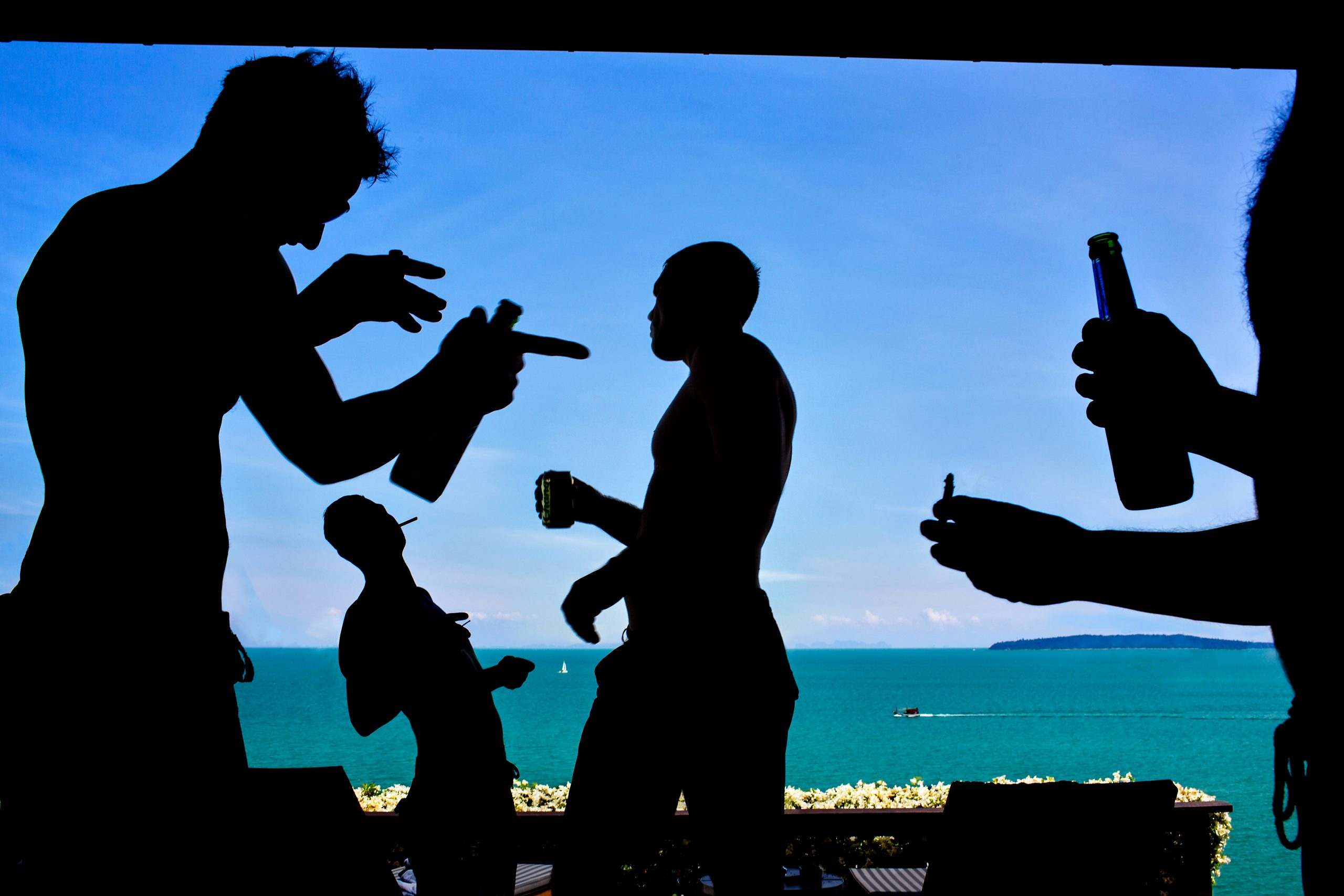 Silhouettes of groomsmen drinking and smoking at beachfront bar