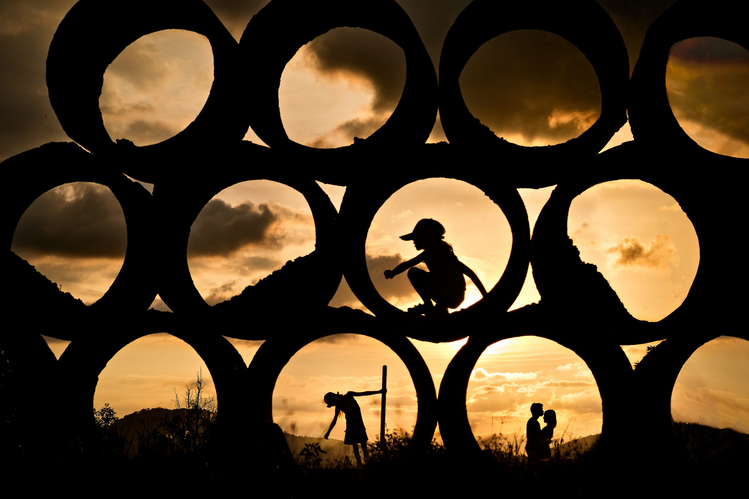 Couple in love kissing with kids playing on construction site silhouetted at sunset in Thailand