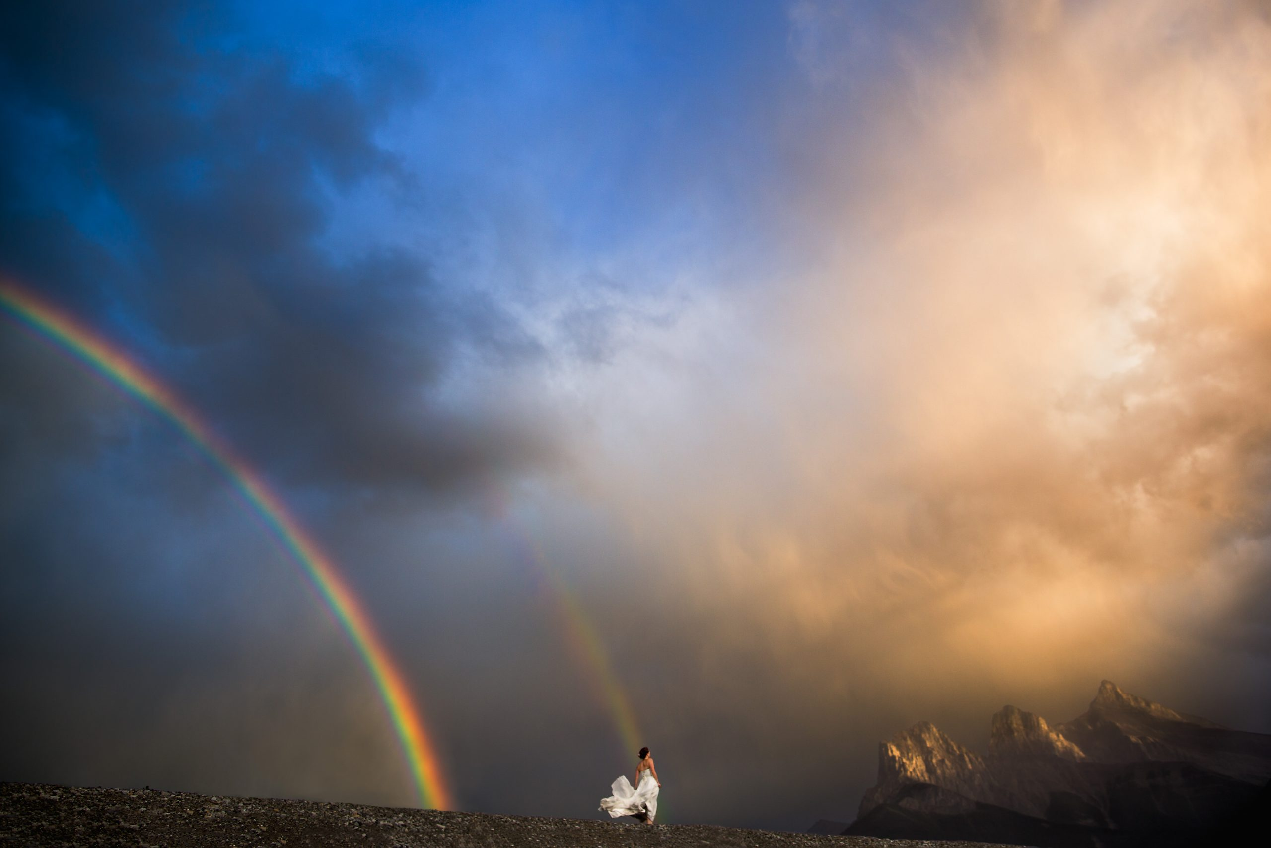 Bride in wedding dressing on mountain top with double rainbow in sky