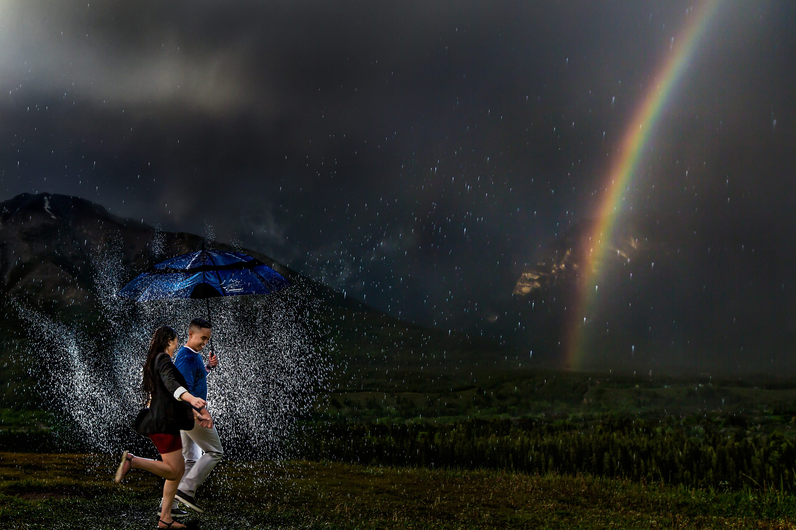 Man and woman run through water holding umbrella to the backdrop of a rainbow