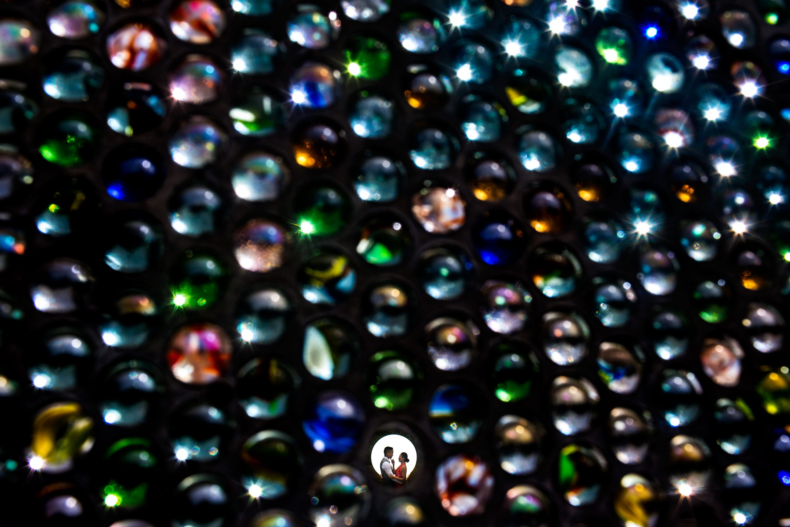 Man and woman looking into each other's eyes is seen through a gap in a wall of beads