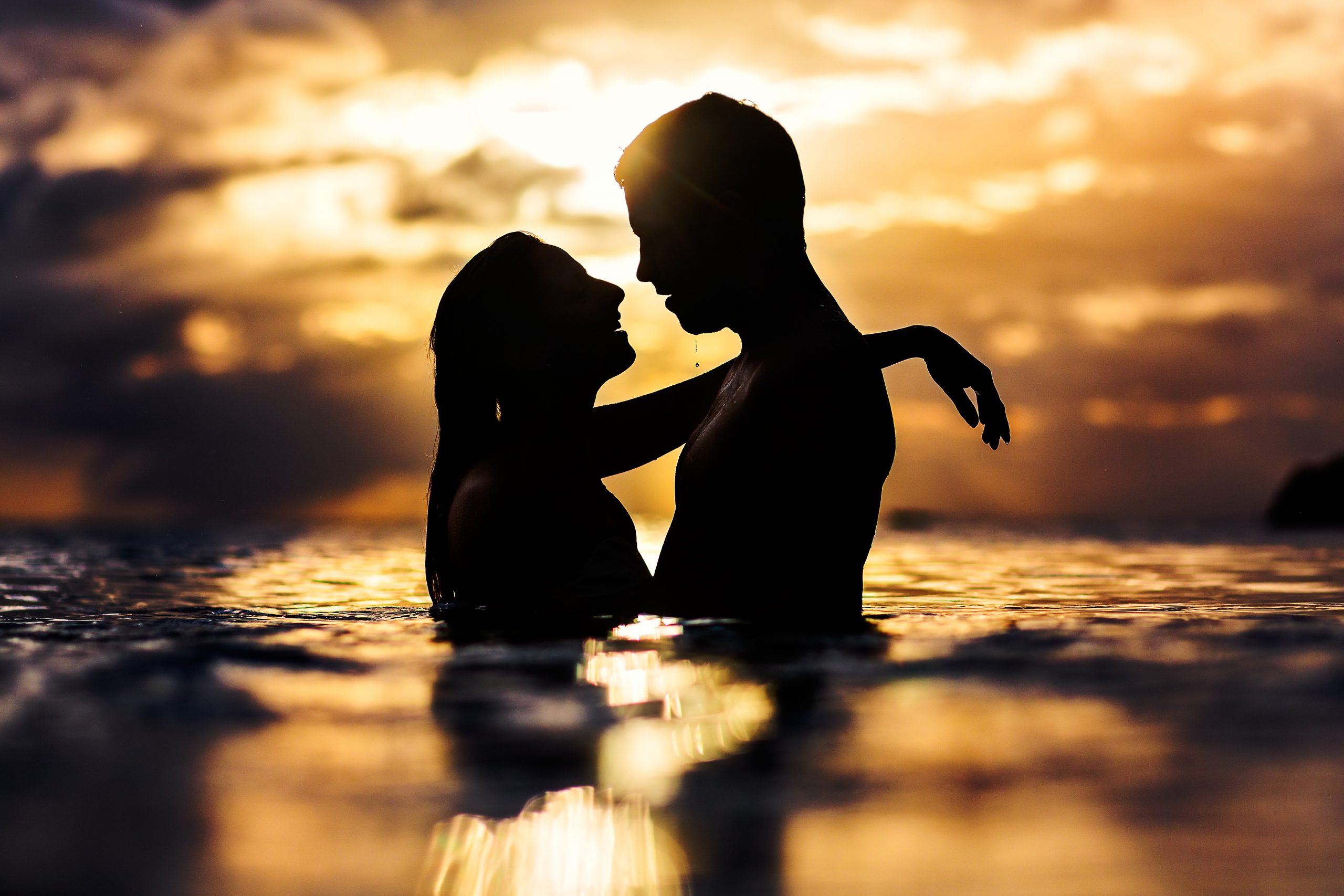 Silhouette of newlyweds looking at each other in seawater at sunset in St. Lucia