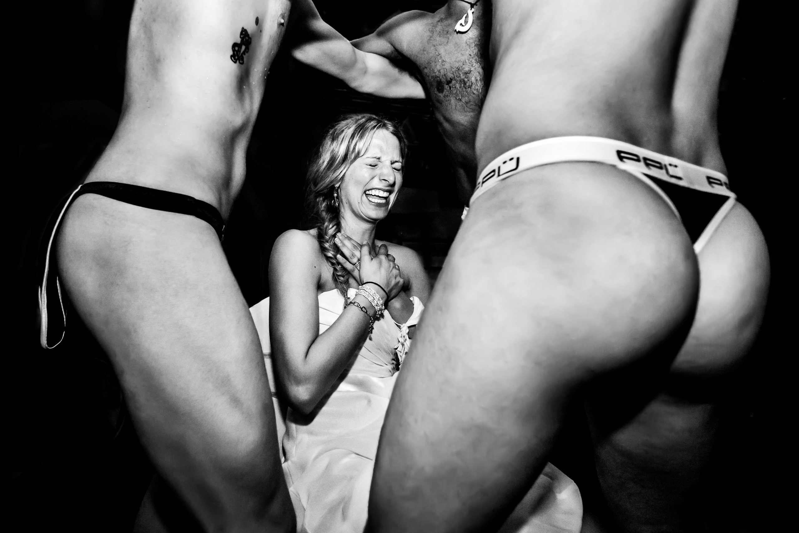 Bride display an embarrassed facial expression because of two men in their underwear