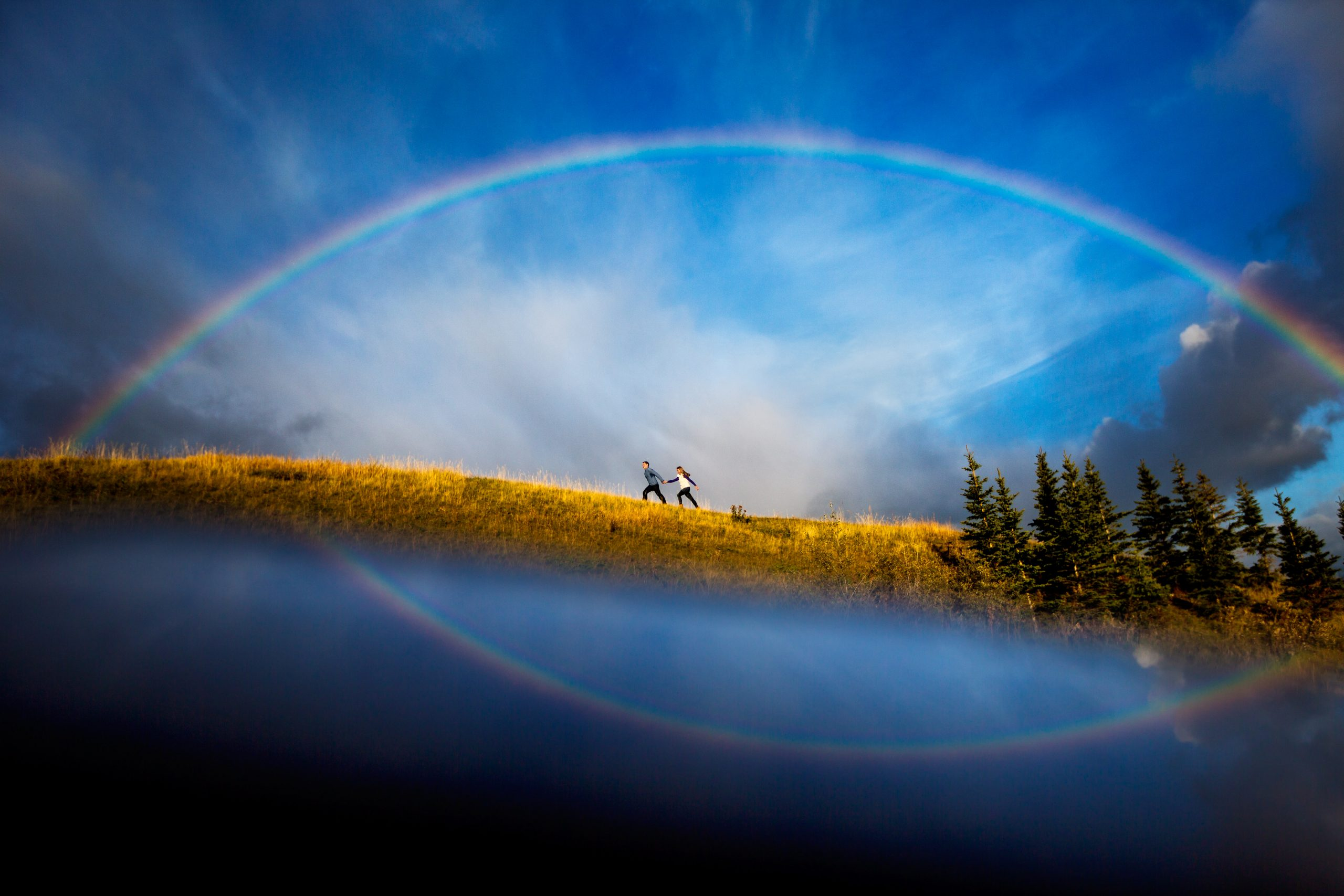A couple holding hands run across a hill with a rainbow in the background
