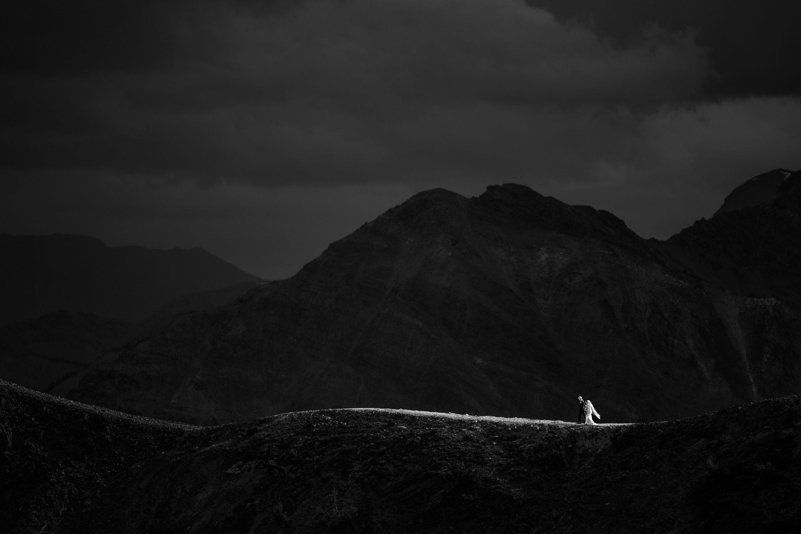 Couple walk along a mountain ridge with a cloudy backdrop