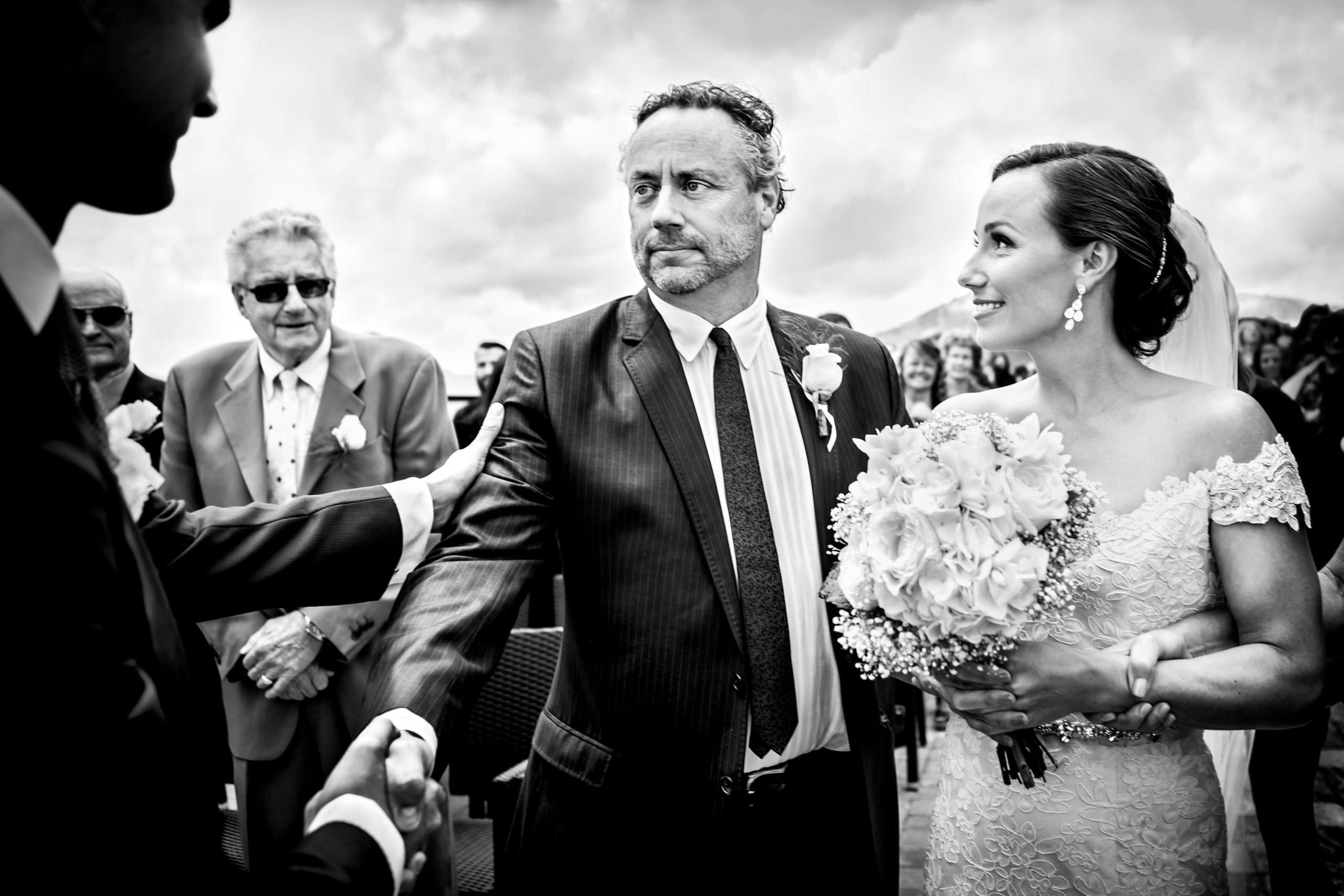 Father shakes the hand of the groom before handing off his daughter during a wedding ceremony