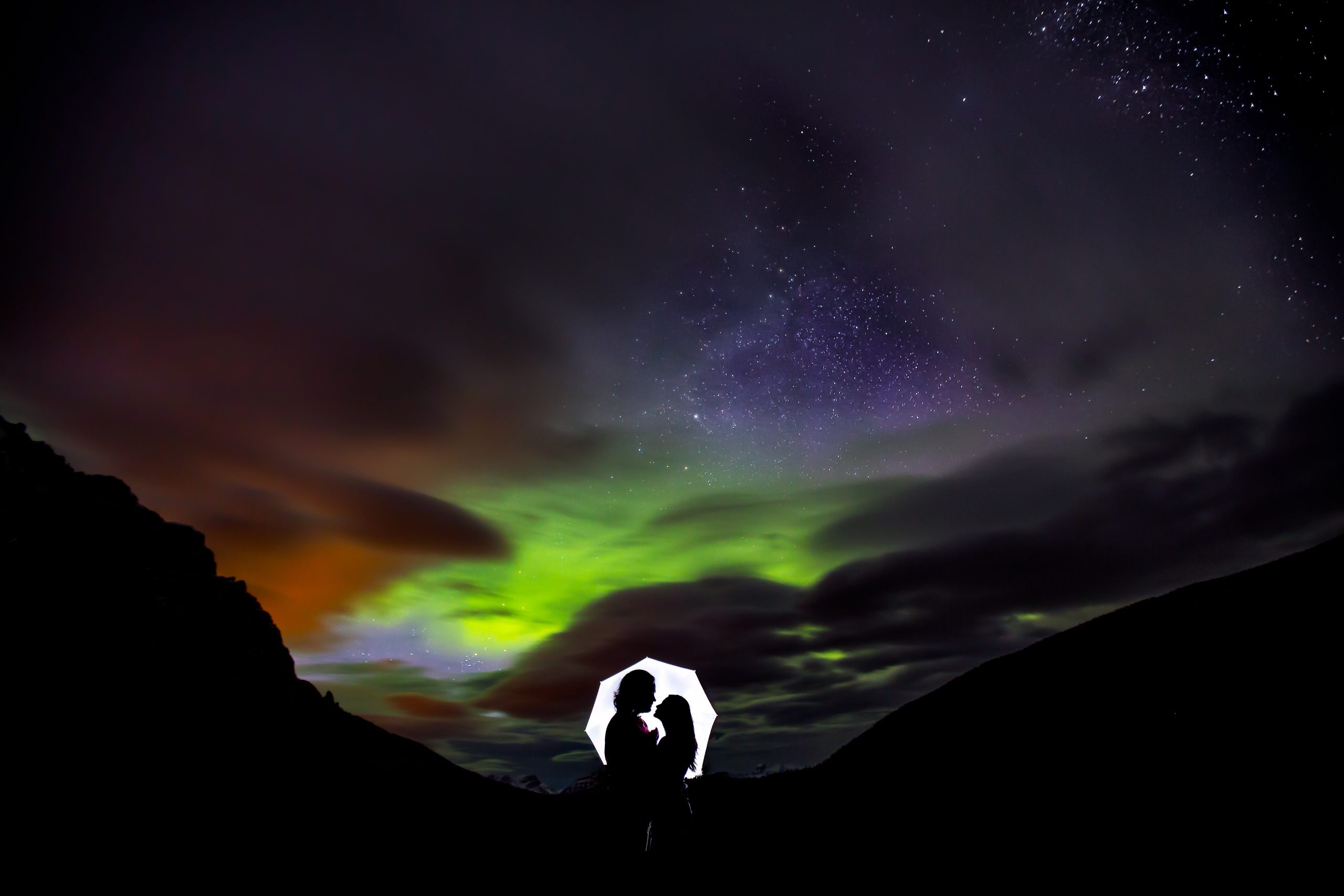 Couple hold each other while aurora borealis illuminates the background