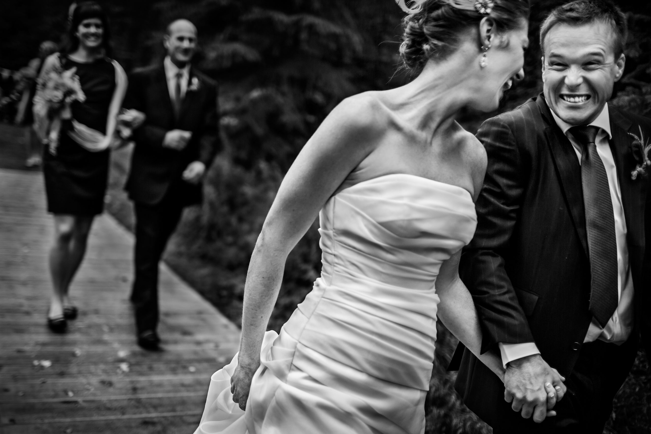 An ecstatic bride and groom walk ahead of bridesmaid and groomsmen