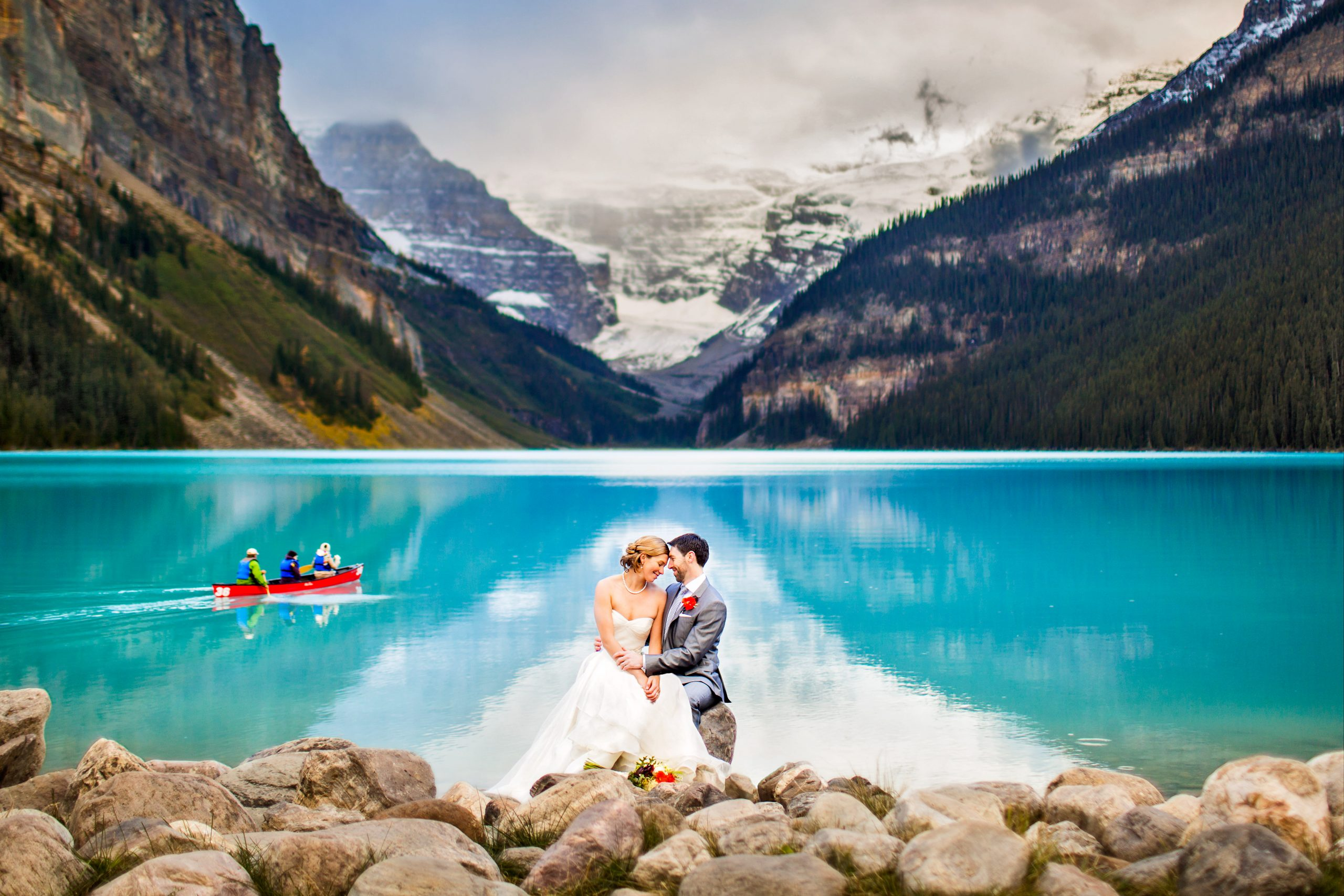 A couple in wedding attire embrace in front of Lake Louise, Banff