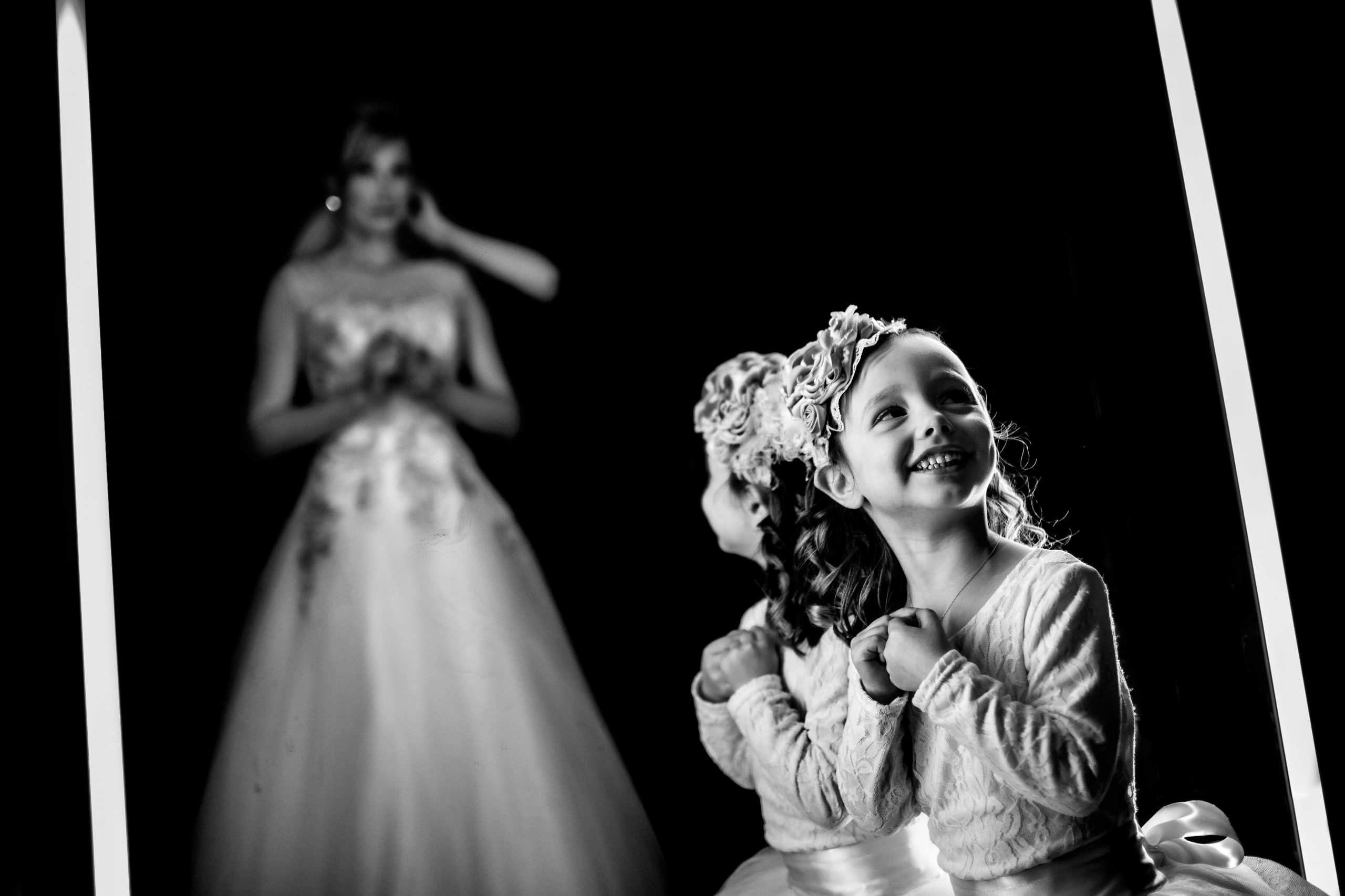 Young girl smiles as she looks at woman in wedding dress