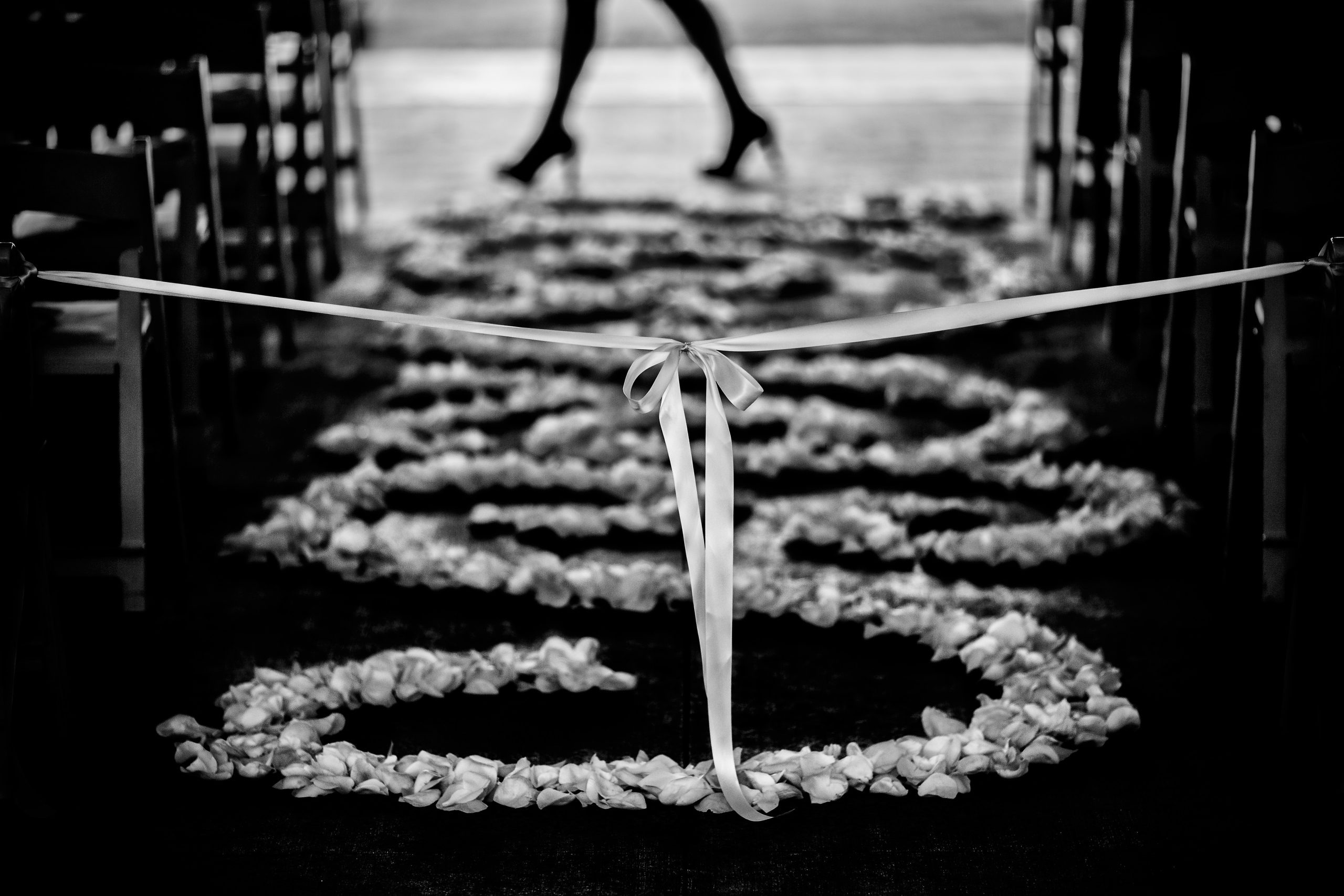 Wedding aisle showered in flower petals is blocked off with a white ribbon as a woman in heels walk across in the background