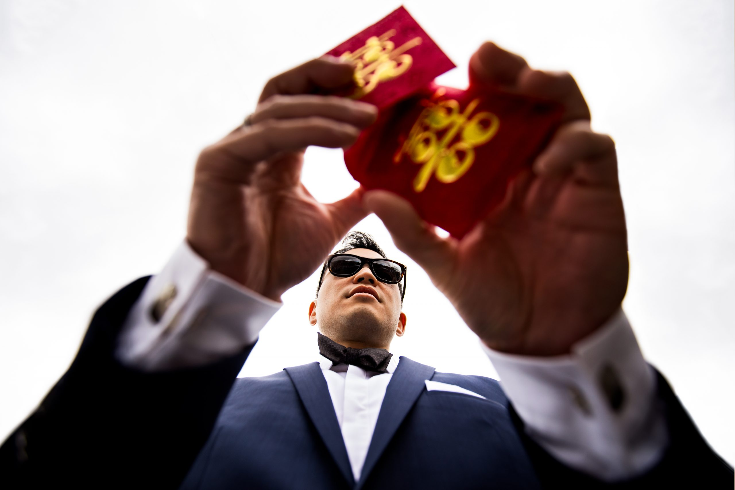 Man in sunglasses and suit holding red envelopes