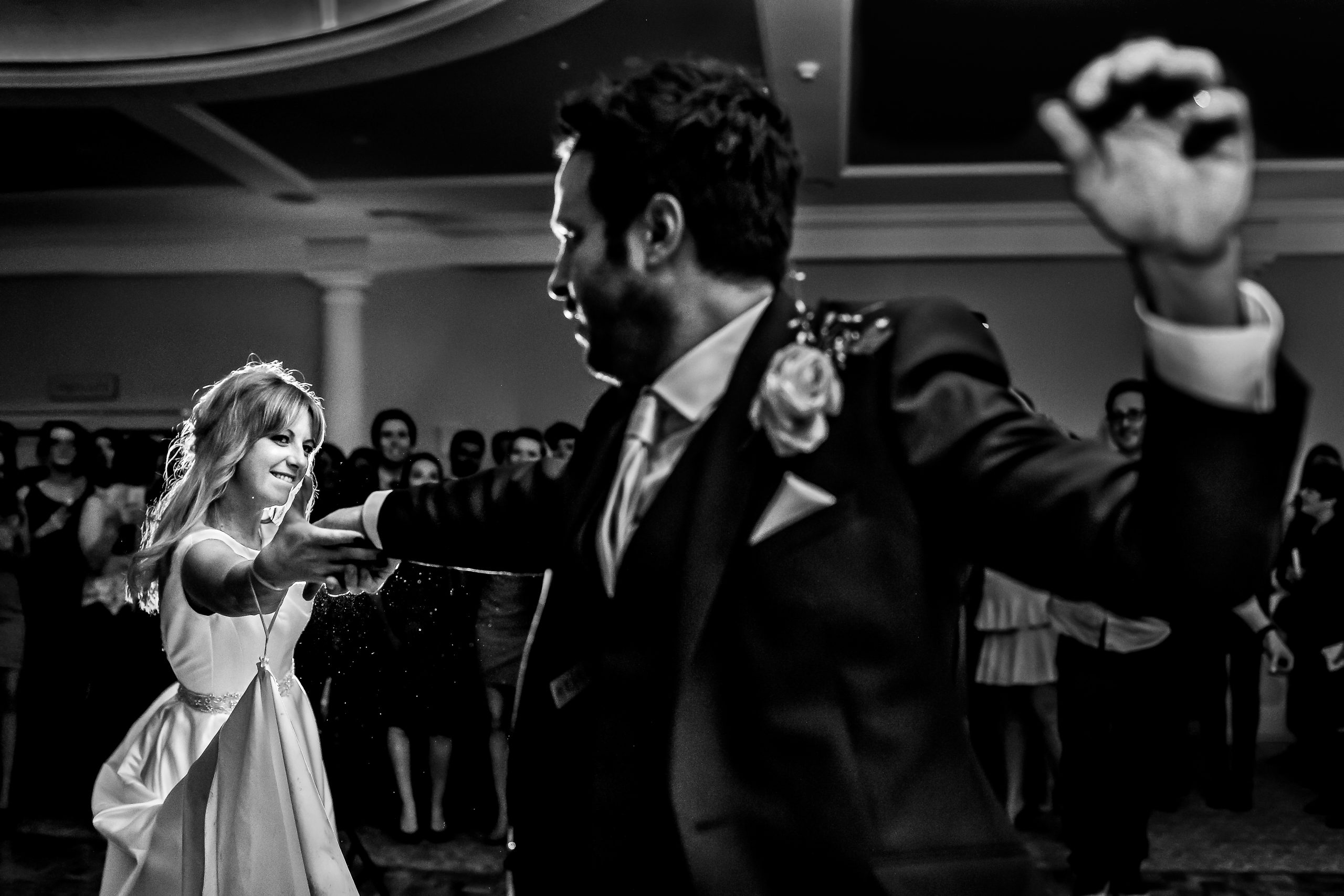 Groom dances with bride as partygoers watch