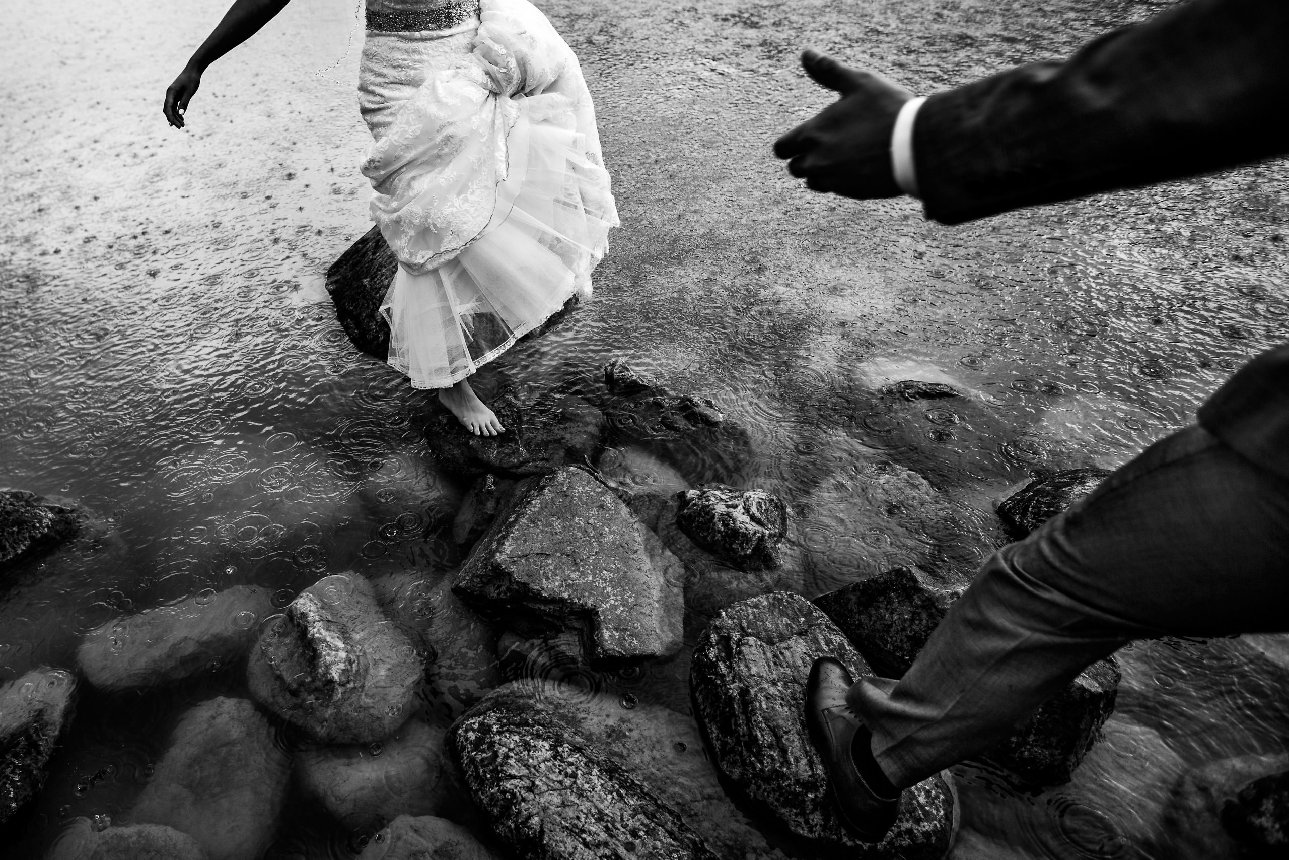 Man offers hand to help bride standing on lakeside rocks as rain drops hit the water