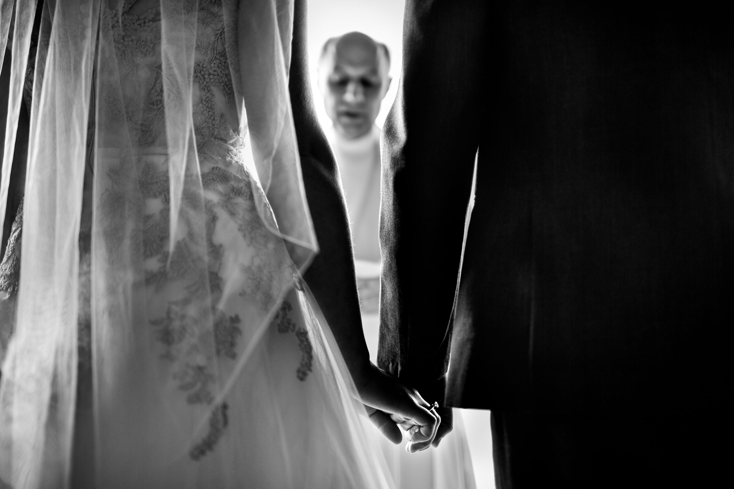 Bride and groom hold hands and between them a priest can be seen
