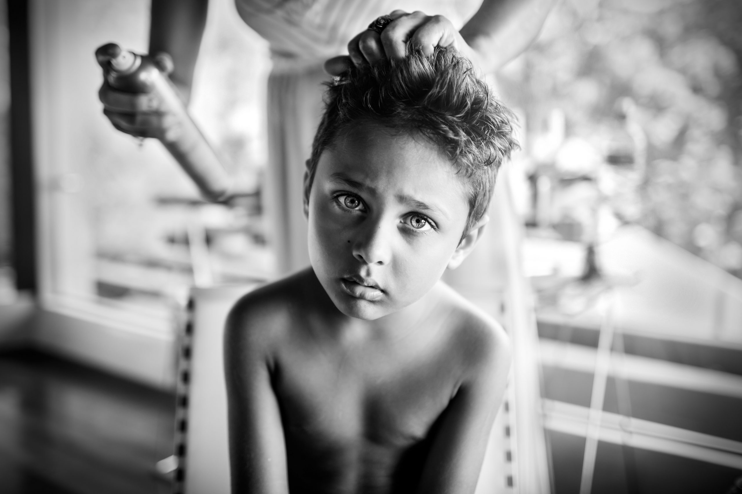 Young boy looks ahead while getting his hair done