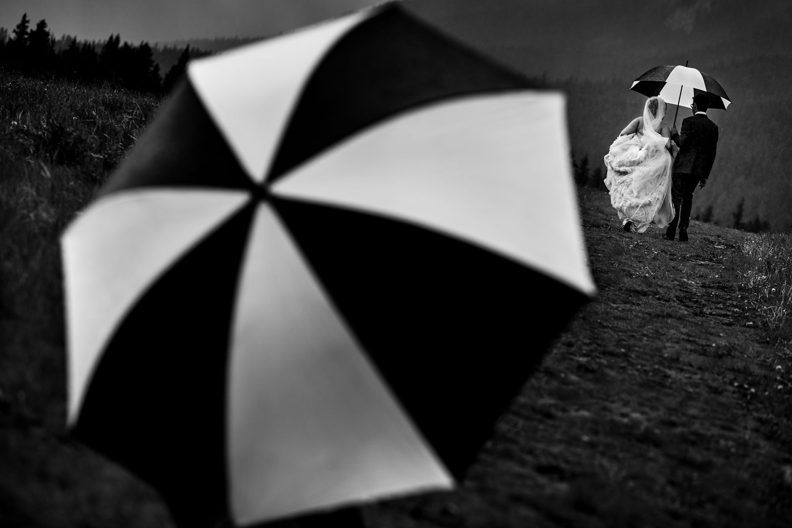 Groom holds an umbrella for bride on a rainy day with another umbrella in the foreground