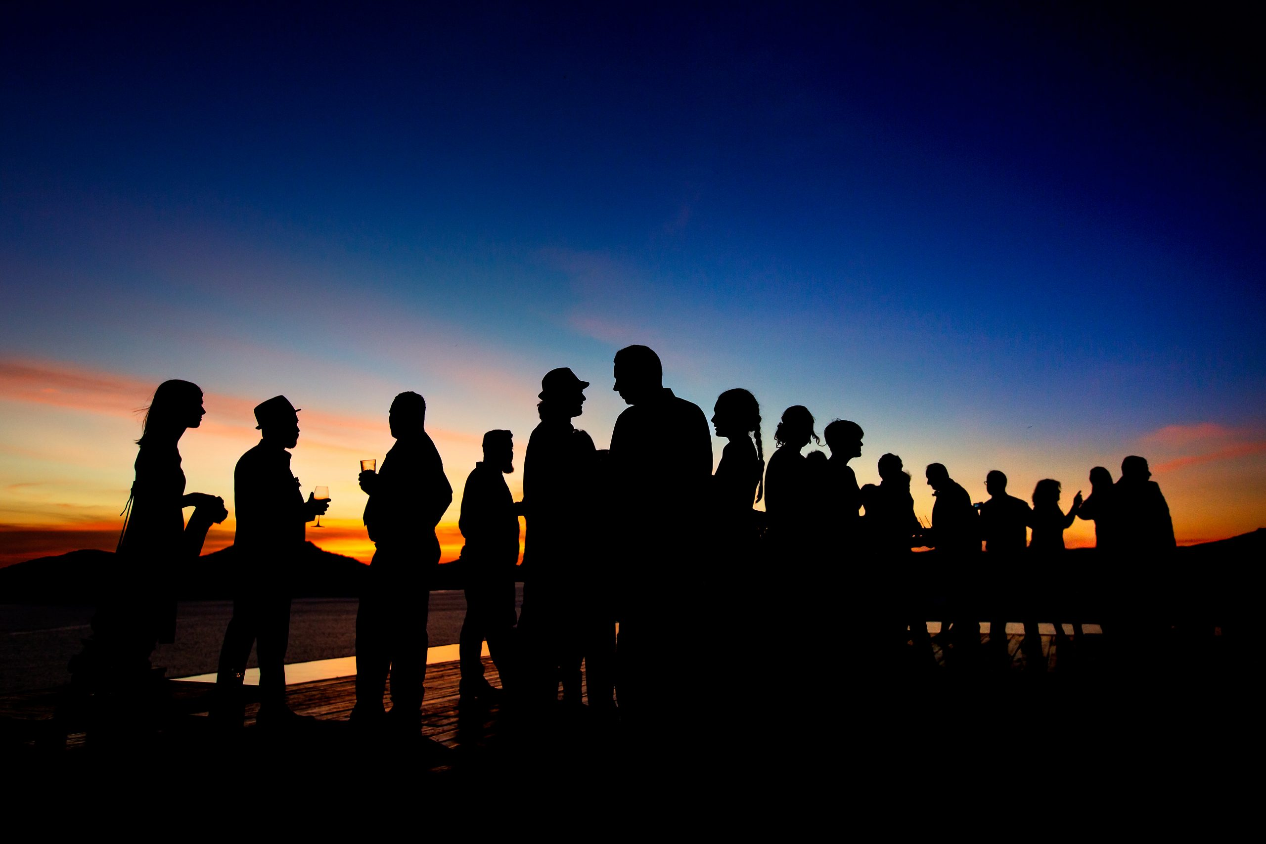 Silhouette of a group of people enjoying drinks in front of a sunset