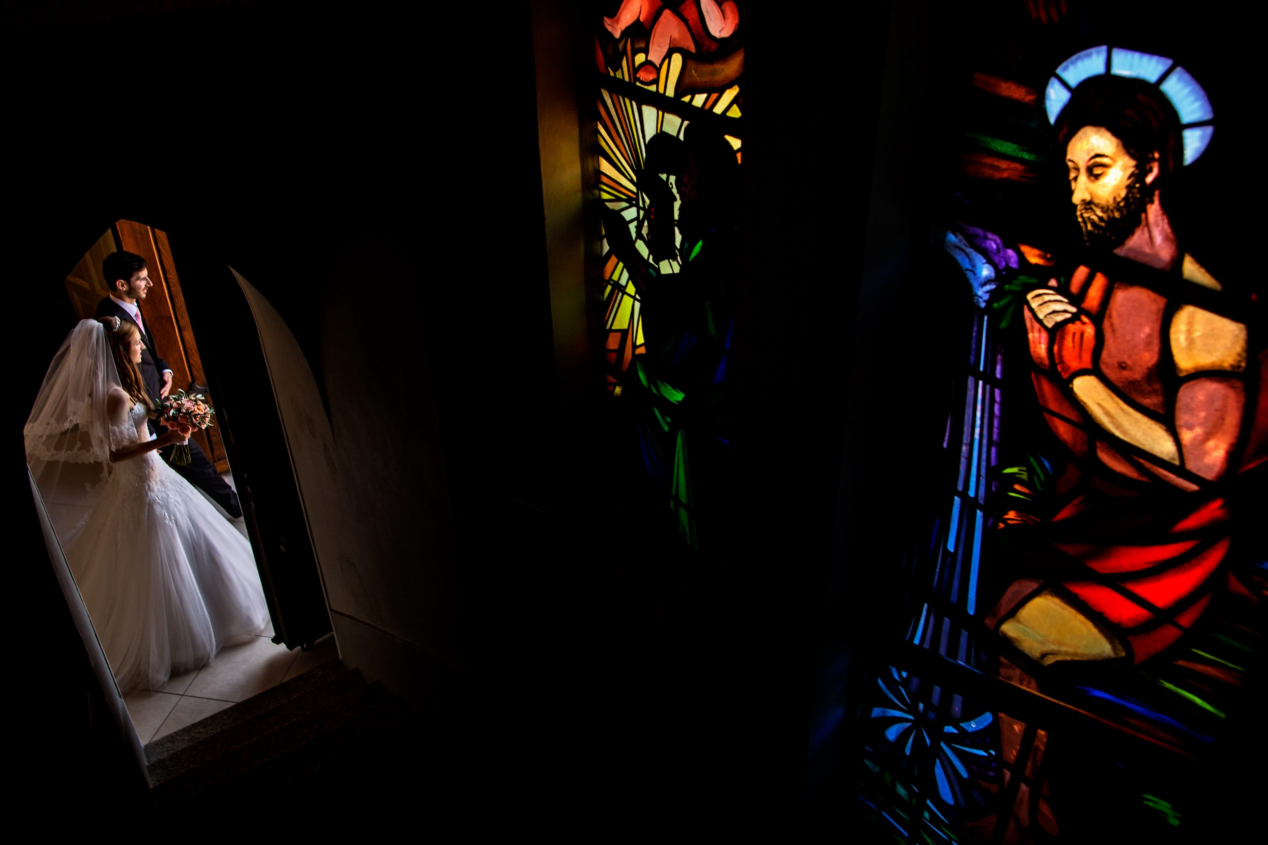 Bride and man walk through a doorway in church with stained glass windows