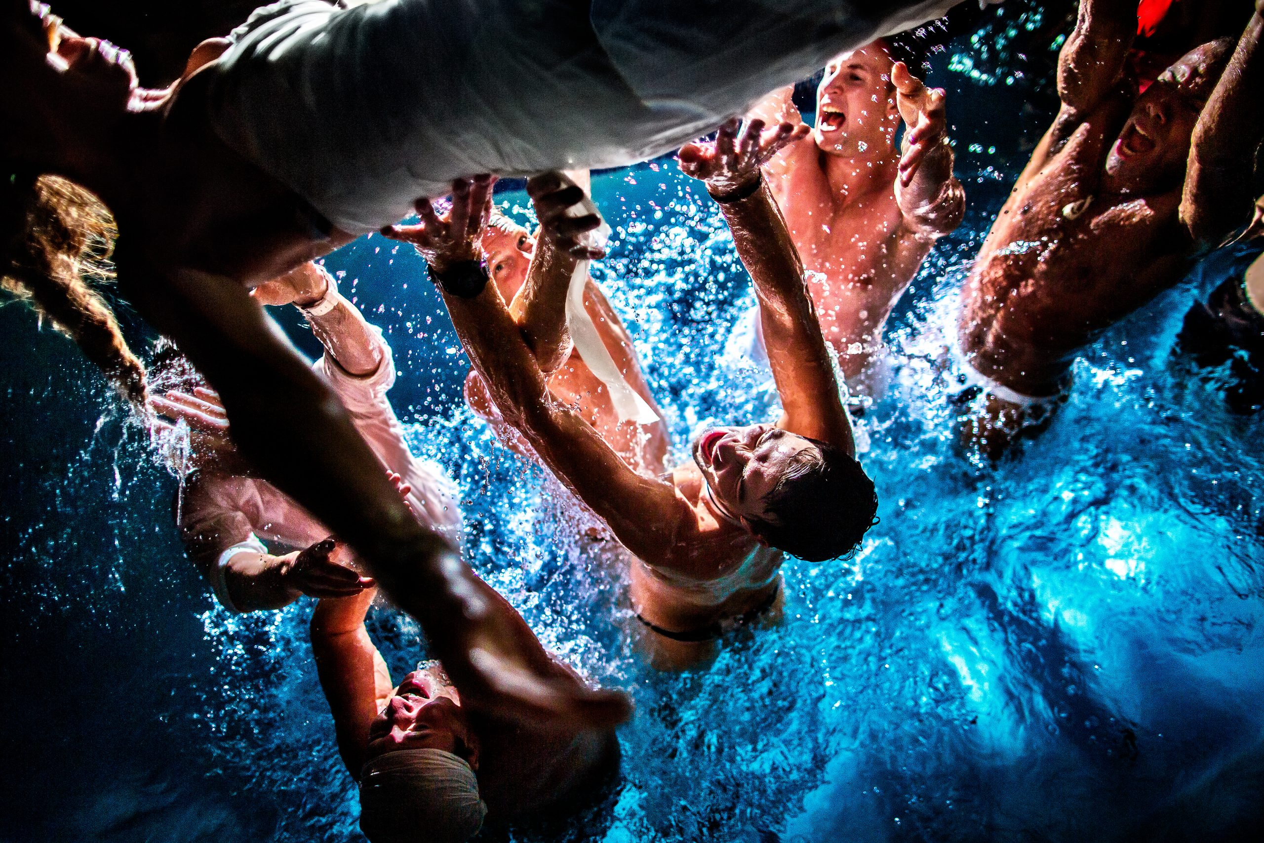 Groom and groomsmen crowd surfing the bride at night in the pool