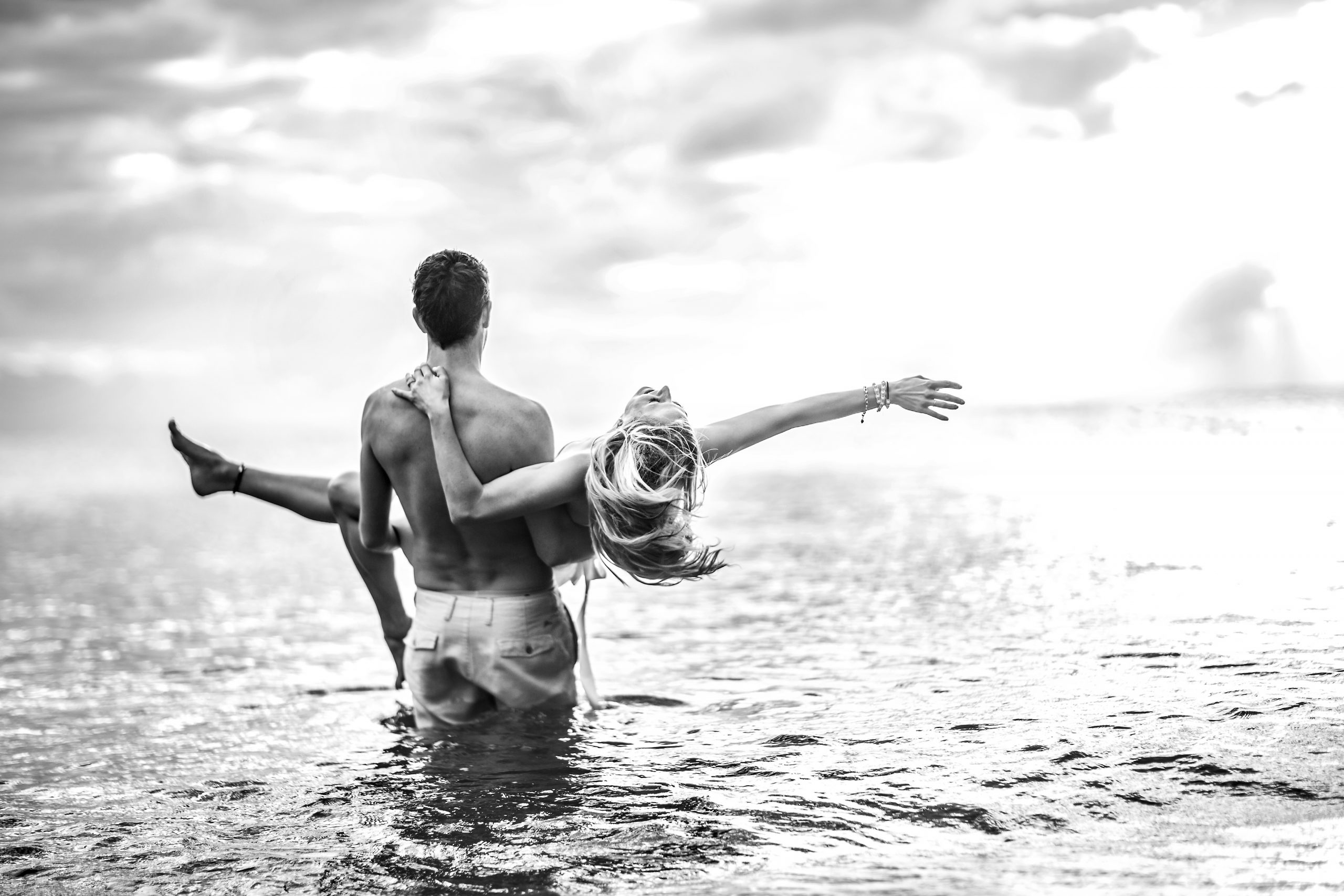 Man holds woman as they walk into a body of water