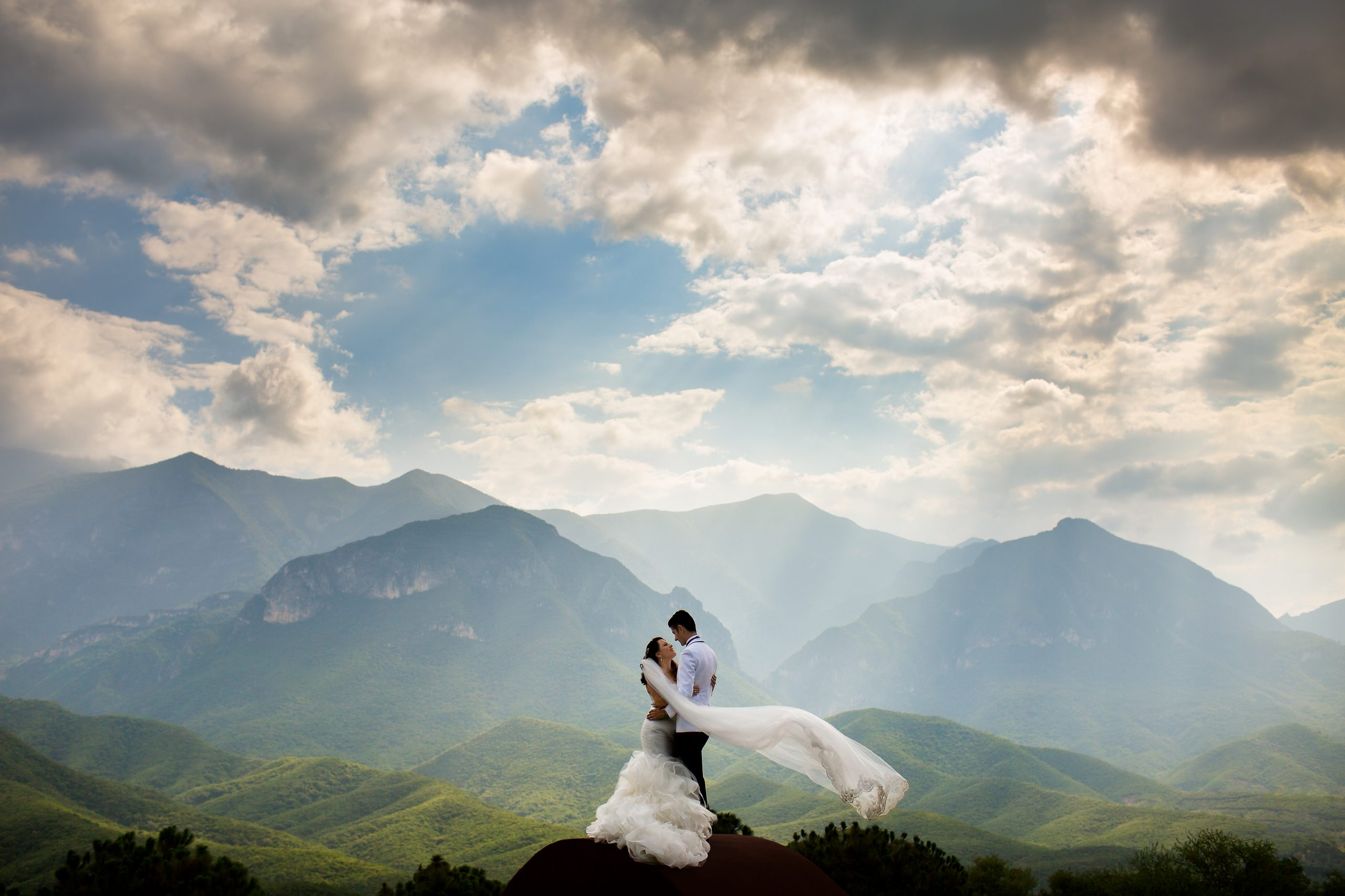 Bride and groom embrace in front of mountain scenery as sun rays shine through clouds
