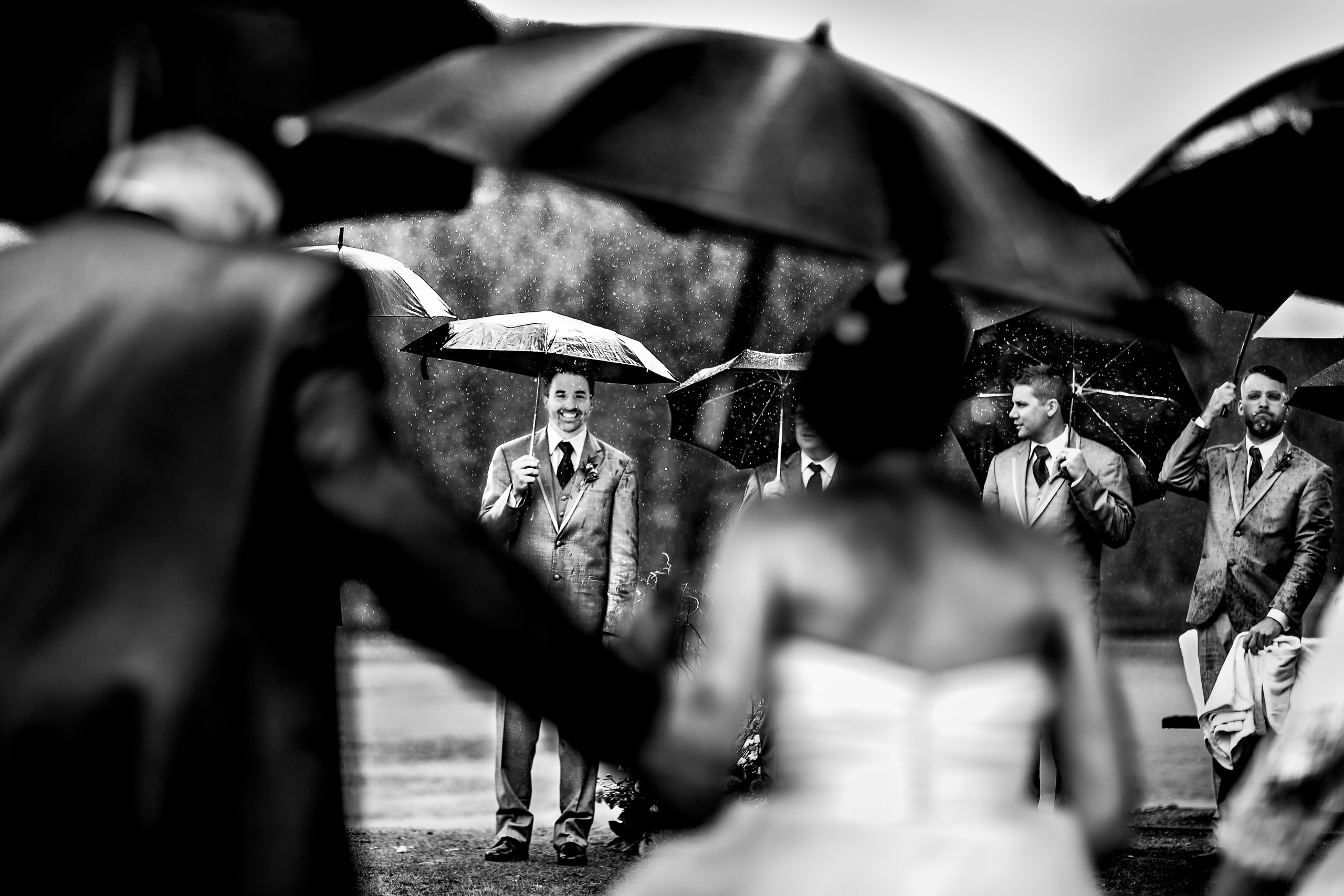 During a rainy day, holding umbrellas, the groom smiles as he sees the bride