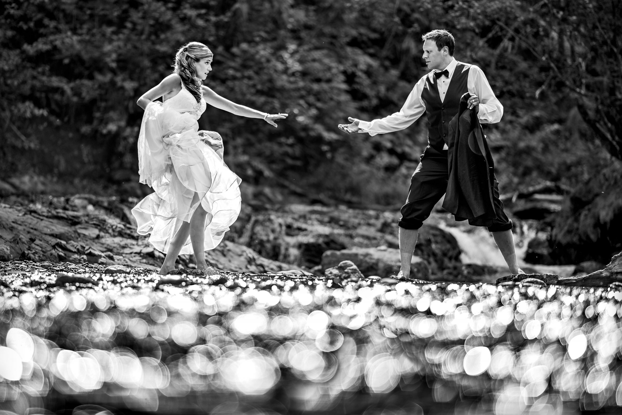 Groom with rolled up pants holds his hand out to help bride cross a stream