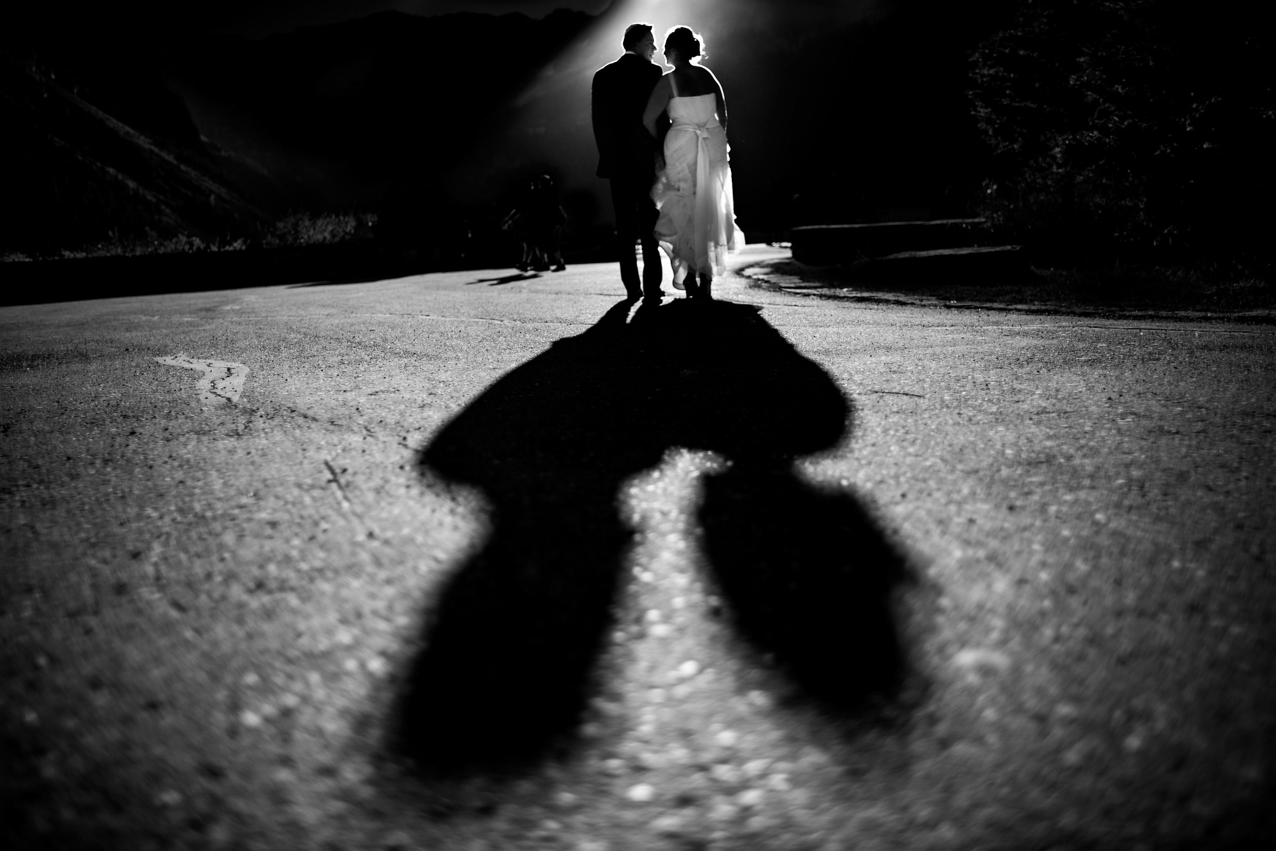Bride and groom walk together as their shadow is cast behind them